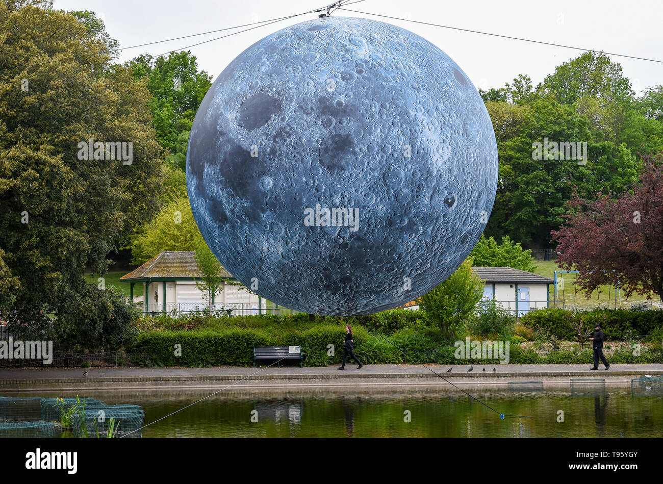 Brighton UK 30th April 2019 - A large model of the moon rises above Queens Park pond in Brighton this morning ready for tonights Brighton Festival event 'Museum of the Moon' by Luke Jerram . The moon will be lit up tonight and over the weekend accompanied by music by composer Dan Jones as it celebrates 50 years since the famous moon landing. Credit: Simon Dack / Alamy Live News Stock Photo