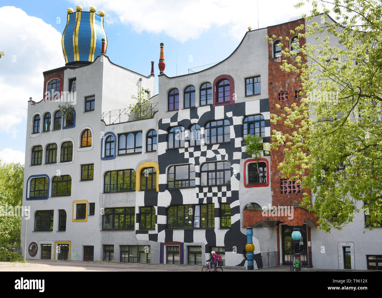 07 May 2019, Saxony-Anhalt, Wittenberg Lutherstadt: The photo shows the Luther-Melanchthon-Gymnasium in Wittenberg, which was rebuilt 20 years ago according to the plans of Friedensreich Hundertwasser (1928-2000). The anniversary in Wittenberg is now being celebrated with a festival week, with exhibitions, theatre performances, concerts and the handover of a green school project. After the fall of the Berlin Wall, students from the city turned directly to the famous Viennese artist and architect with the request to transform the GDR prefabricated building into a very special place. At present - Stock Image
