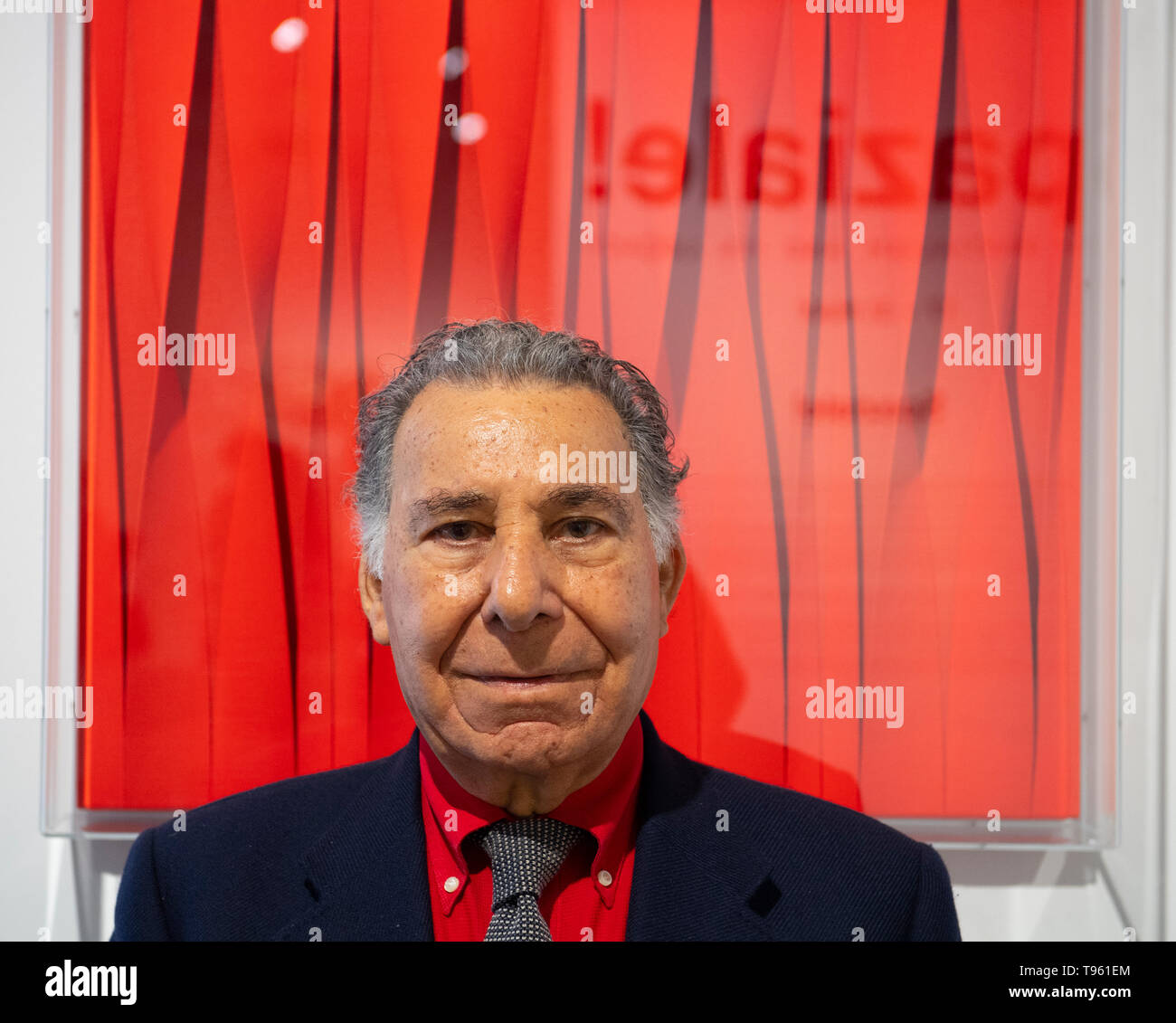 Opera Gallery, New Bond Street, London, UK. 17th May 2019. Organised in collaboration with the Italian Embassy in London, the exhibition includes 40 iconic canvases by Lucio Fontana, Agostino Bonalumi and Enrico Castellani among others, tapping into the unprecedented attention Italian post-war art is currently receiving. Image: Pino Manos, one of the last surviving artists of Spatialism, in front of his canvas Sincronicita rosso vibrante, 2018. Credit: Malcolm Park/Alamy Live News. - Stock Image