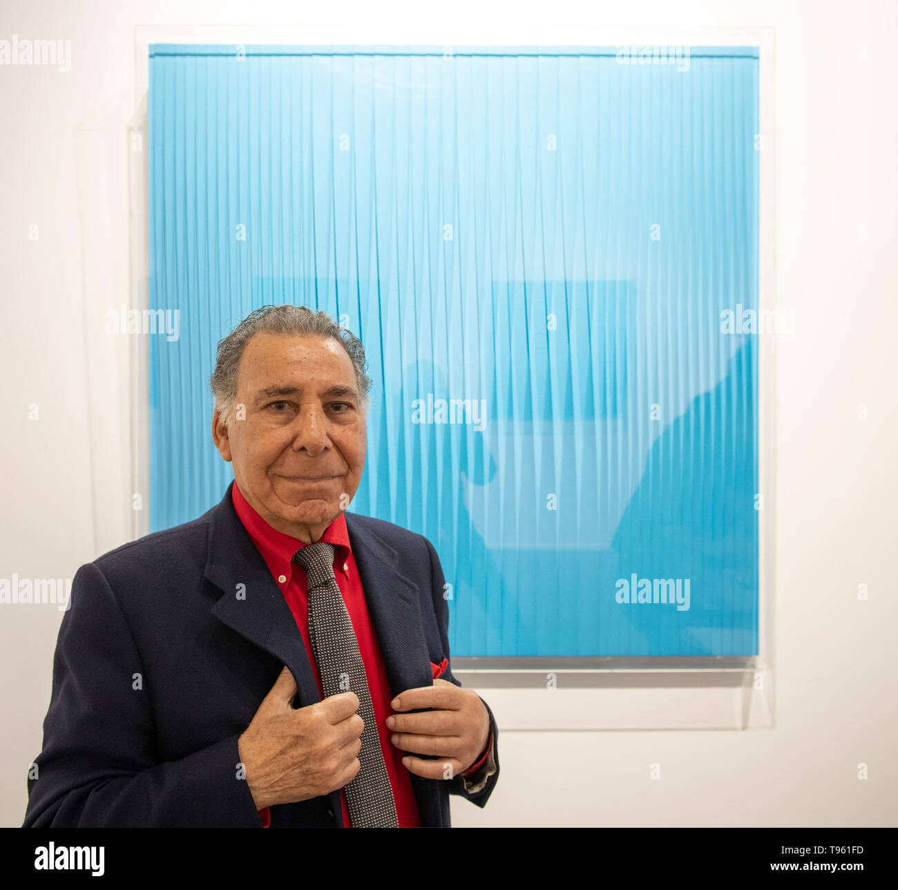 Opera Gallery, New Bond Street, London, UK. 17th May 2019. Organised in collaboration with the Italian Embassy in London, the exhibition includes 40 iconic canvases by Lucio Fontana, Agostino Bonalumi and Enrico Castellani among others, tapping into the unprecedented attention Italian post-war art is currently receiving. Image: Pino Manos, one of the last surviving artists of Spatialism, in front of his canvas Sincronicità blu reale, 2018. Credit: Malcolm Park/Alamy Live News. - Stock Image
