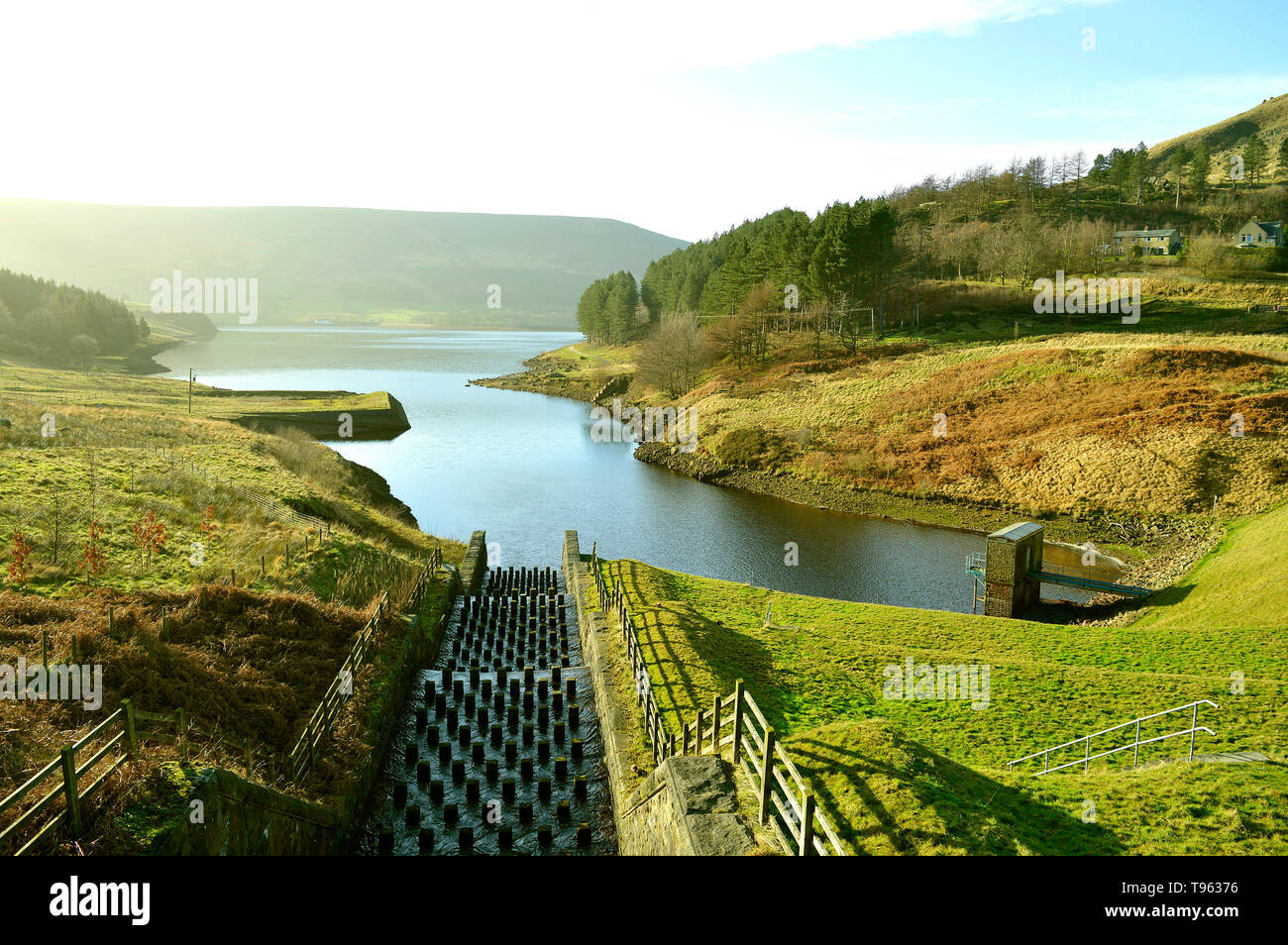 The overflow stepped spillway from Yeoman Hey Reservoir into Dovestone Reservoir on a misty sunny day - Stock Image