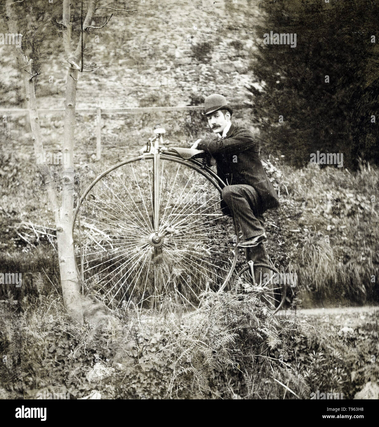 An antique bicycle; American; about 1891. The penny-farthing, also known as a high wheel, high wheeler and ordinary, is a type of bicycle with a large front wheel and a much smaller rear wheel. It was popular after the 'boneshaker' until the development of the safety bicycle in the 1880s. It was the first machine to be called a 'bicycle.' - Stock Image