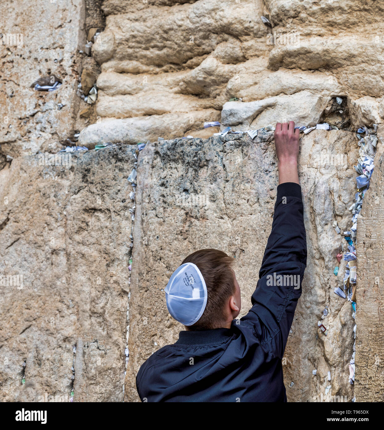 Jerusalem,israel,27-march-2019: Jewish man prays next to a crack filled with letters containing written prayers at the Western Wall in Jerusalem. Israel Stock Photo
