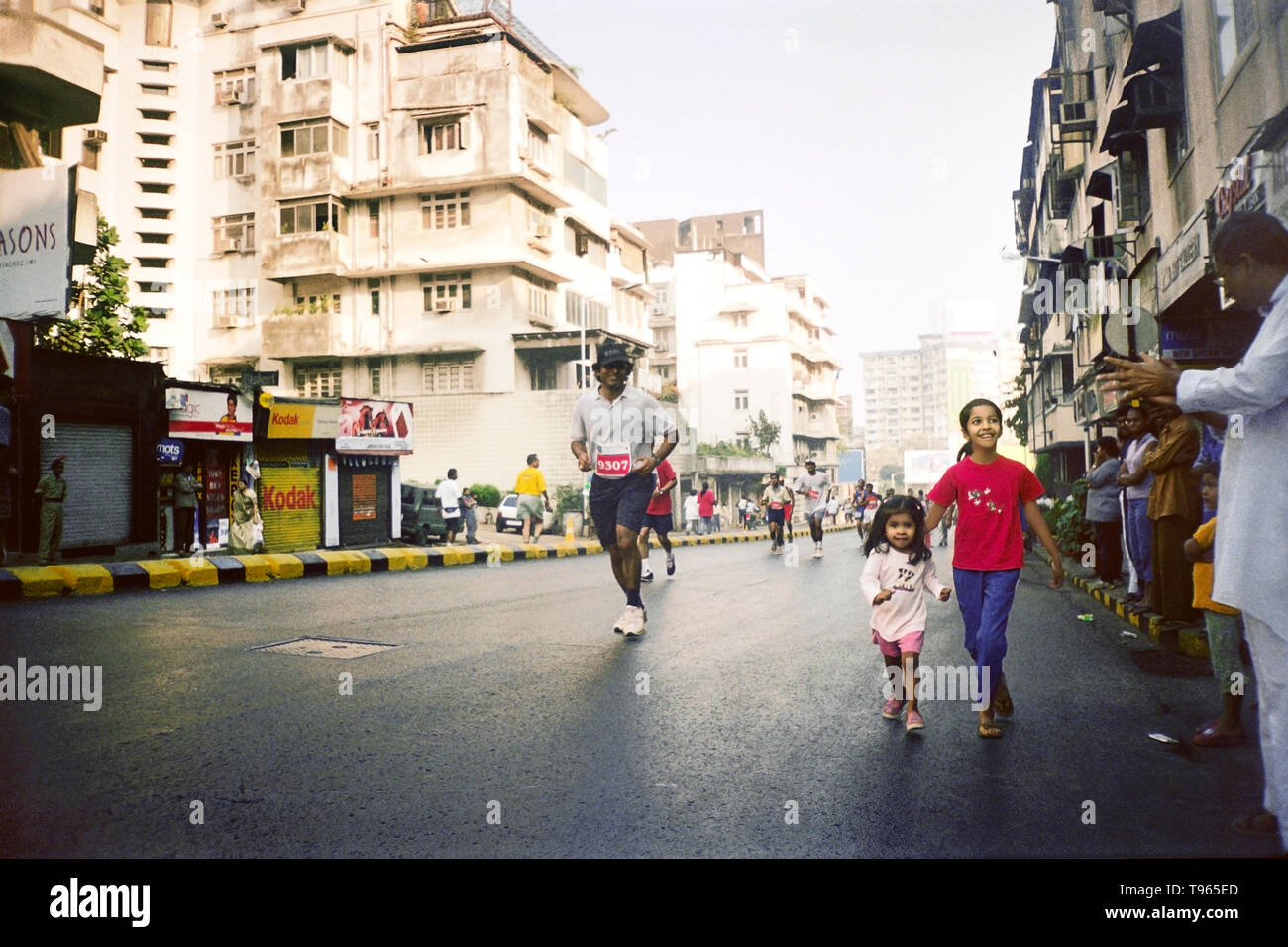 Young infant girl and her sister running alongside the runners of the  MUMBAI MARATHON 2005 - Stock Image