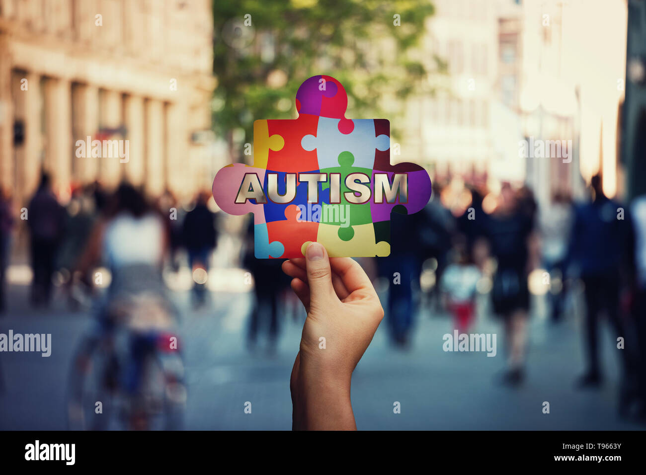 I am not alone symbol of Autism as a child hand holding a colorful puzzle piece over a crowded street background. Social awareness, autistic education - Stock Image