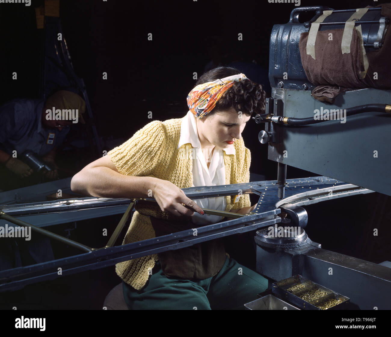 A girl riveting machine operator at the Douglas Aircraft Company plant joins sections of wing ribs to reinforce the inner wing assemblies of B-17F heavy bombers, Long Beach, Calif. Better known as the Flying Fortress, the B-17F bomber is a later model of the B-17, which distinguished itself in action in the south Pacific, over Germany and elsewhere. It is a long range, high altitude, heavy bomber, with a crew of seven to nine men - and with armament sufficient to defend itself on daylight missions. Although the image of 'Rosie the Riveter' reflected the industrial work of welders and riveters, - Stock Image