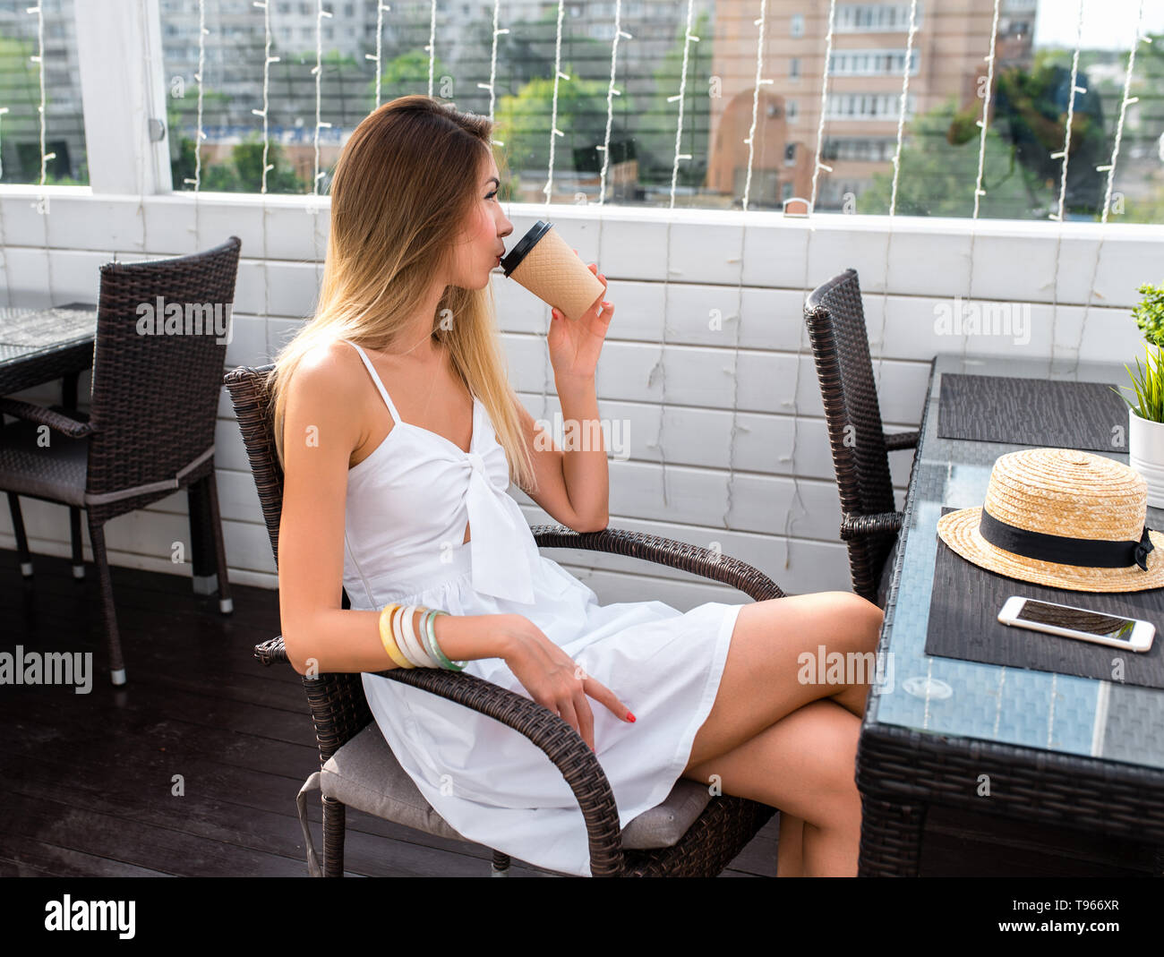 Woman in white dress, drinking coffee tea, breakfast lunch, snack restaurant, summer cafe, sitting. Dreaming thoughts, happy looking, resting after - Stock Image