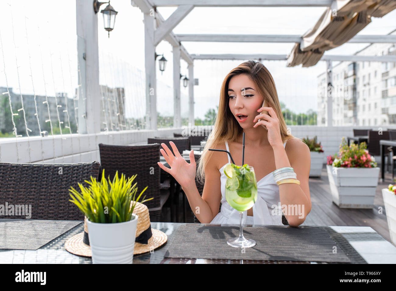 Woman white dress summer cafe calling phone, surprised shock, bewilderment. Surprise delight, conversation smartphone. Breakfast lunch snack - Stock Image