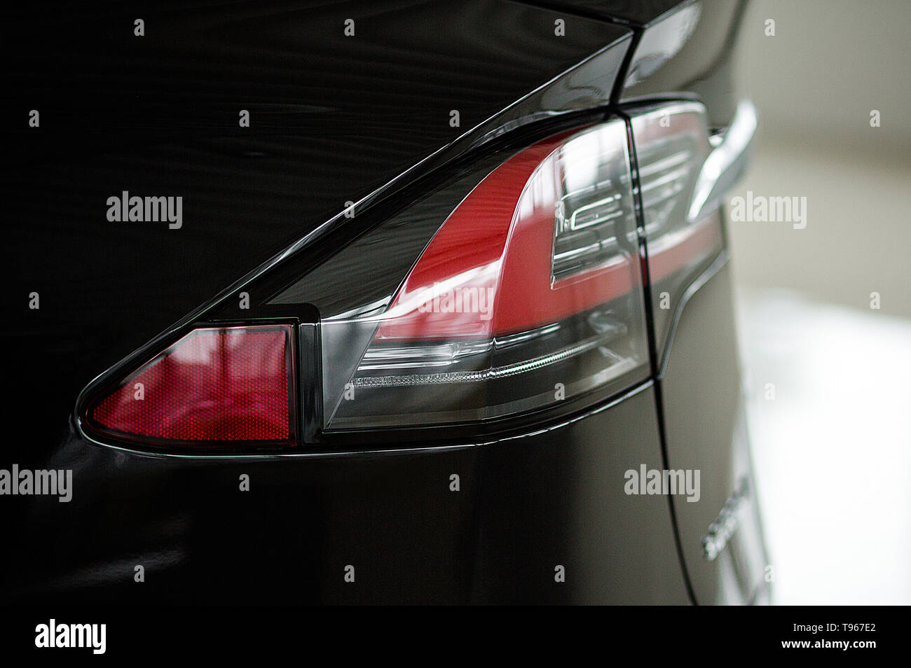 Red Rear Lights of Automobile Close-Up. Tail Lightening System of Beautiful Brand New Tesla in Black Color. Kyiv, Ukraine, F-Drive showroom 13 of febr - Stock Image