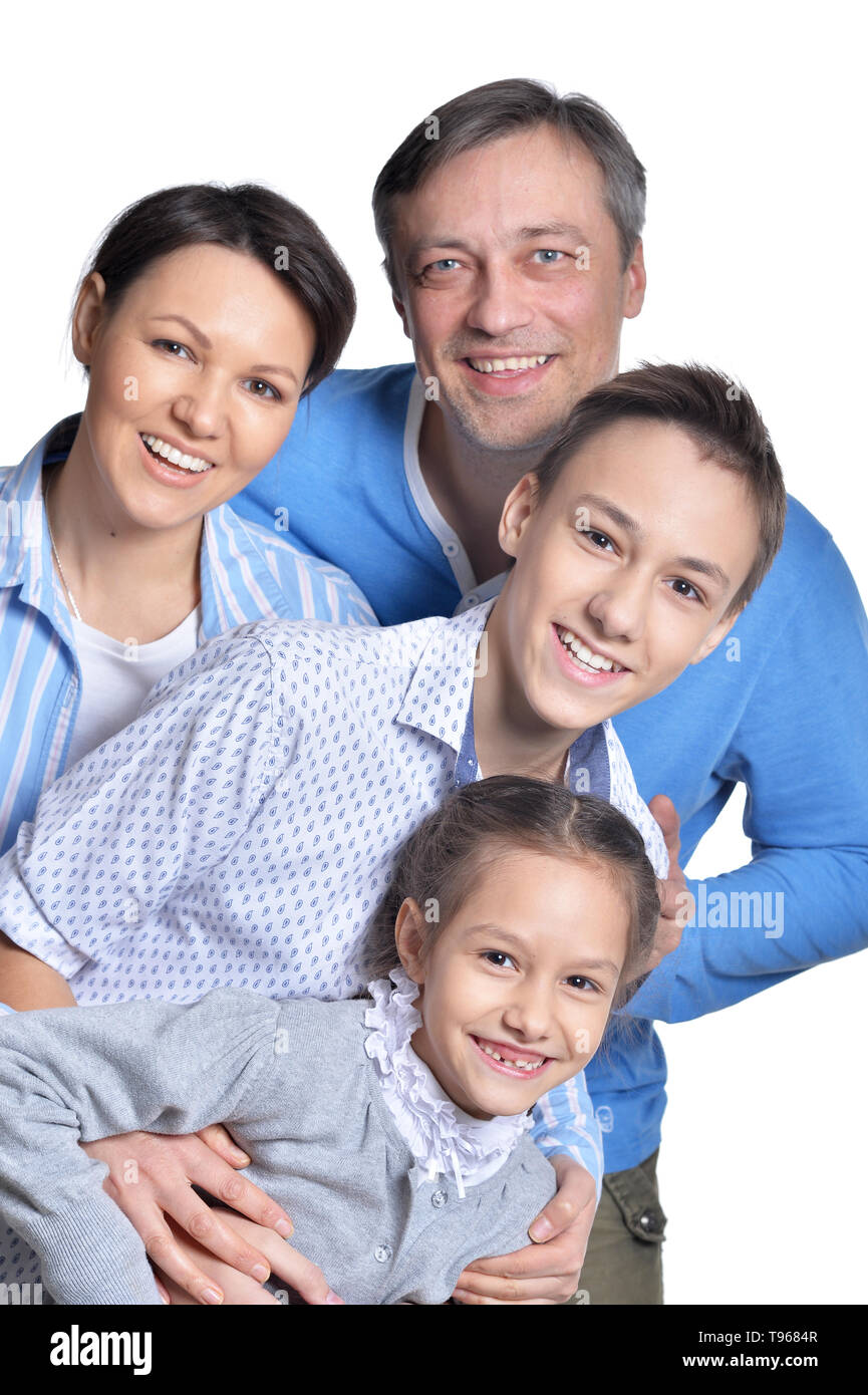 Happy smiling family of four posing together on white - Stock Image