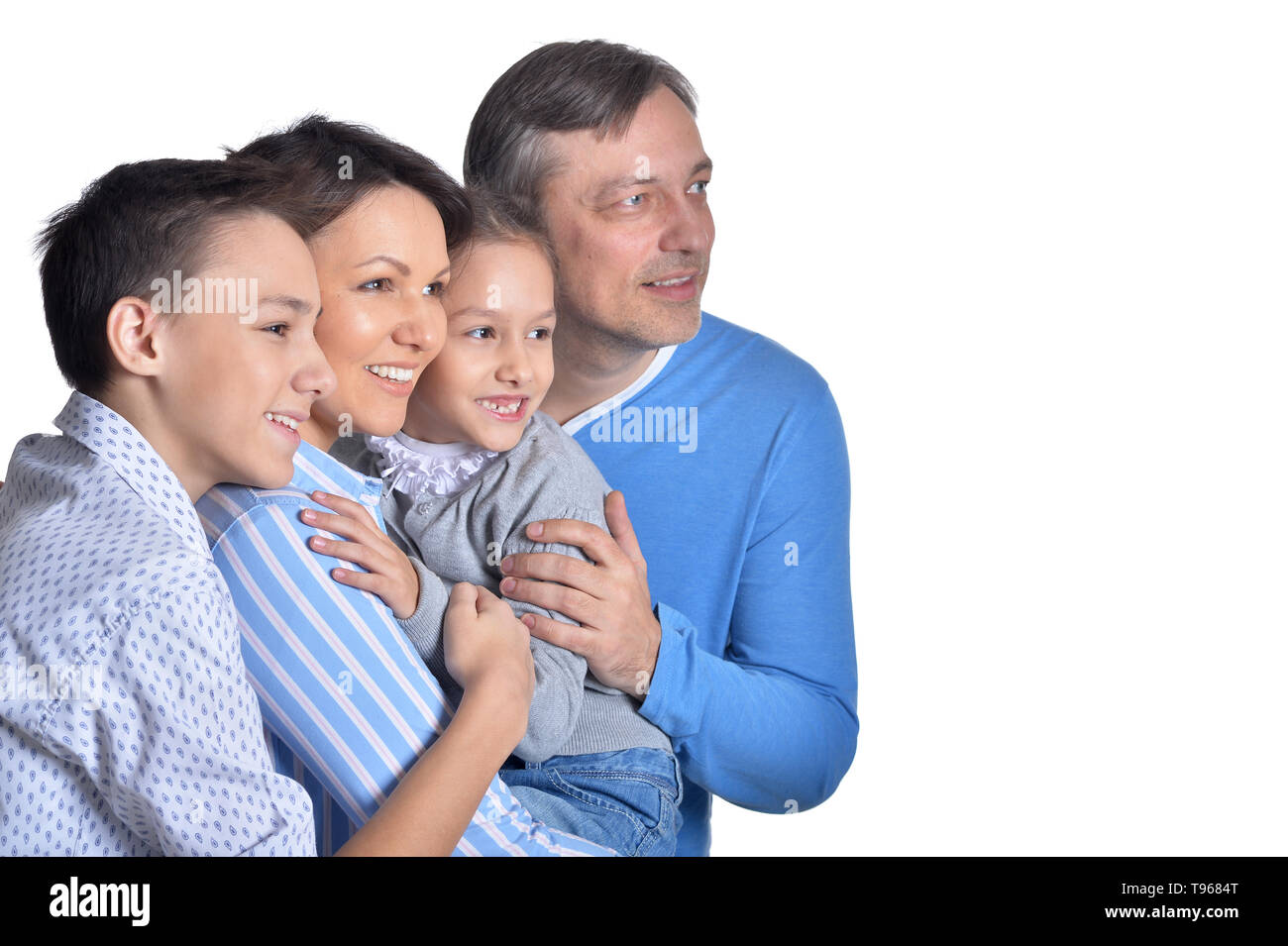 Happy smiling family of four posing together on white background - Stock Image