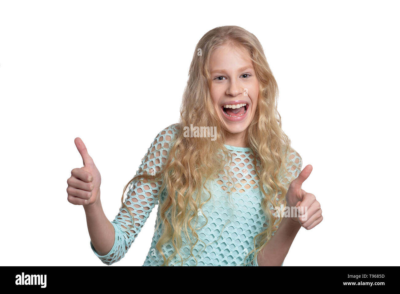Portrait of cute blonde teen girl showing thumbs up isolated on white background - Stock Image
