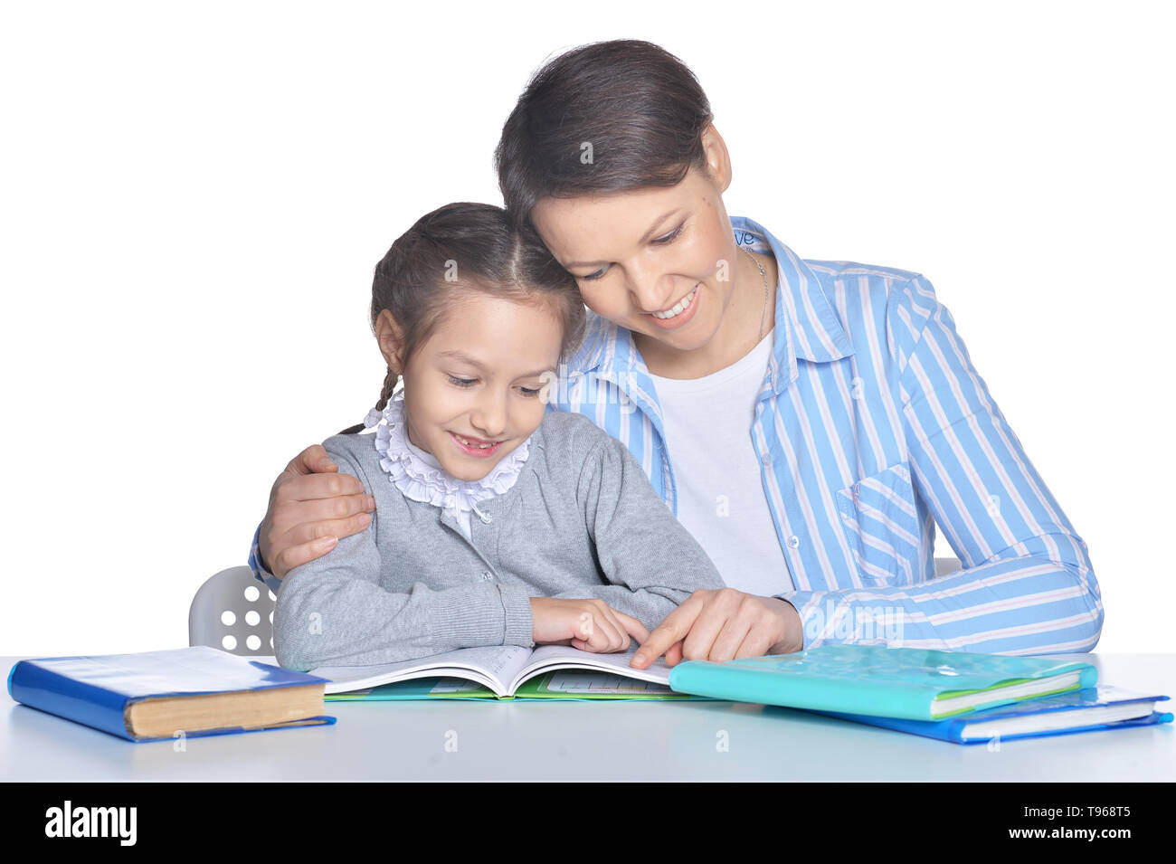 Mother with daughter reading books against white - Stock Image