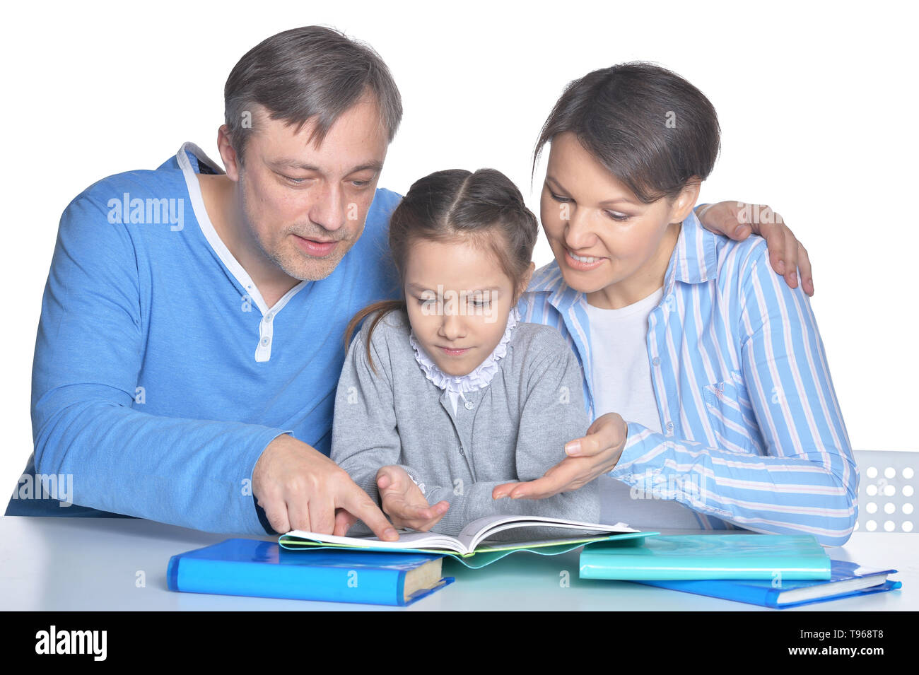 Parents with beutiful daughter reading books against white - Stock Image