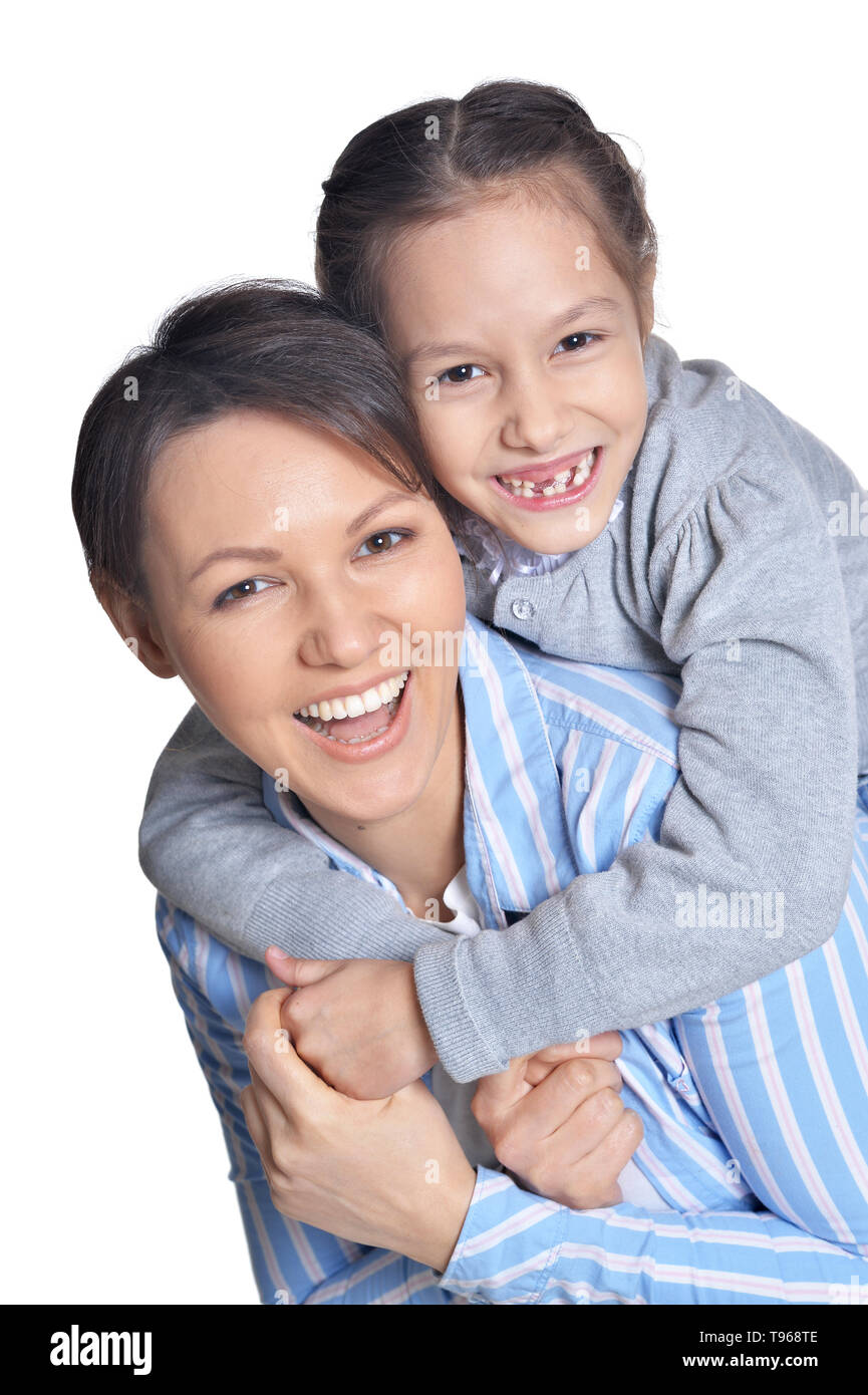 Happy mother with beautiful daughter posing against white - Stock Image