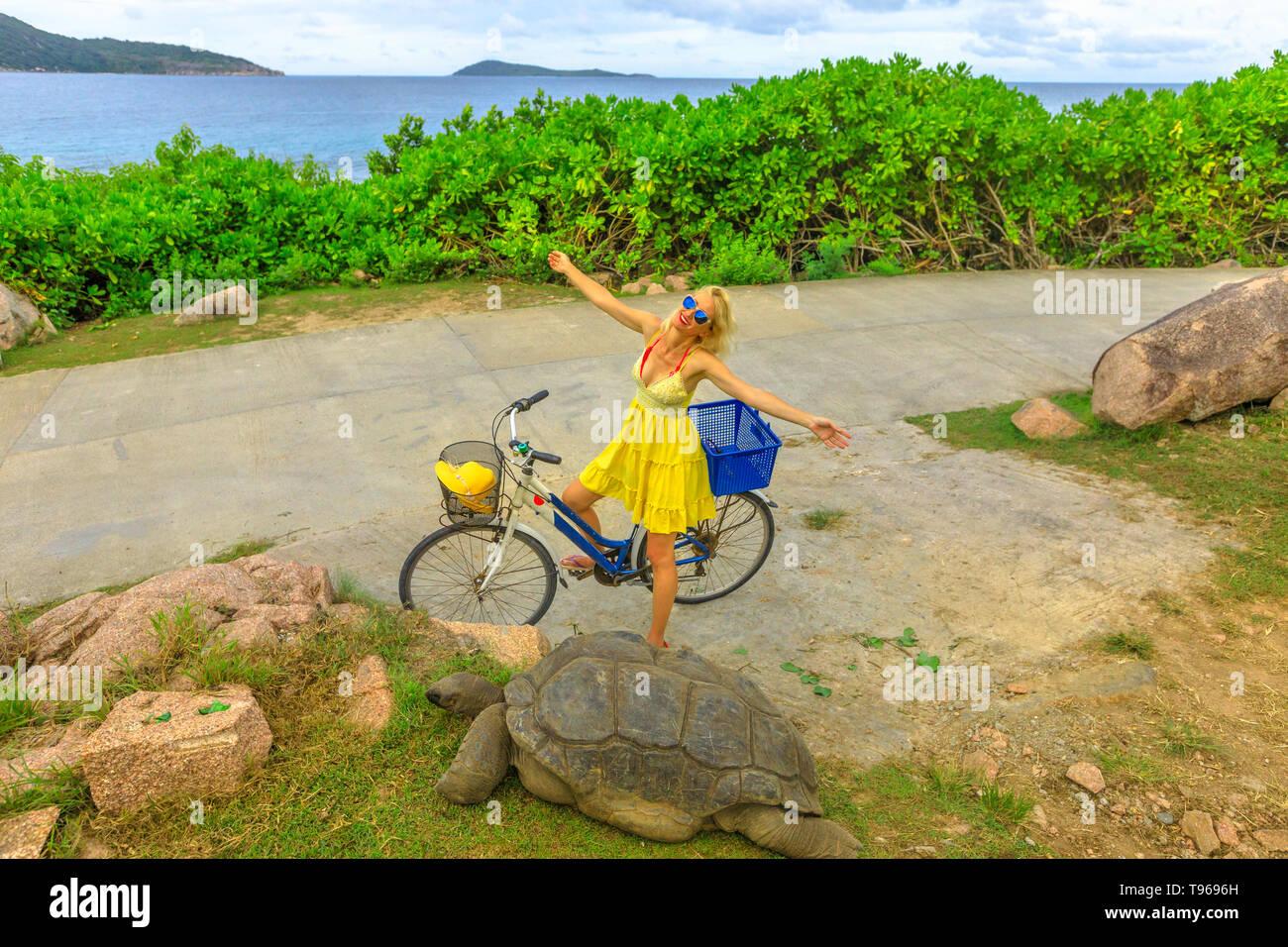 Happy caucasian lifestyle tourist woman on bicycle near Anse Banane in La Digue, Seychelles, with Aldabra Giant Tortoise, Aldabrachelys gigantea - Stock Image