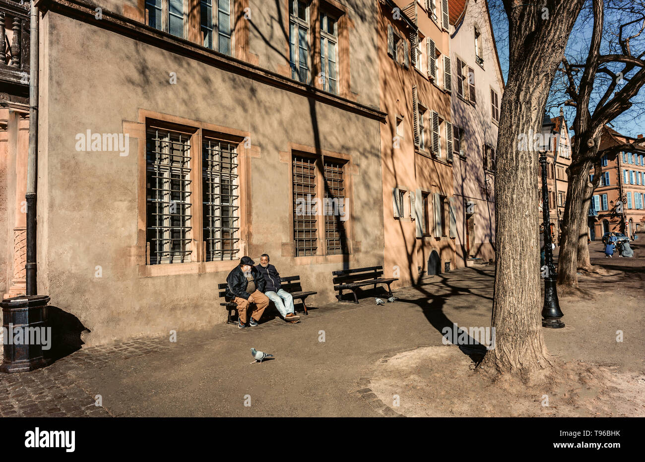 Colmar, Alsace, France, February 24, 2019. Cozy and beautiful streets of the French city on a sunny spring warm day. Two old man are sitting on the be - Stock Image