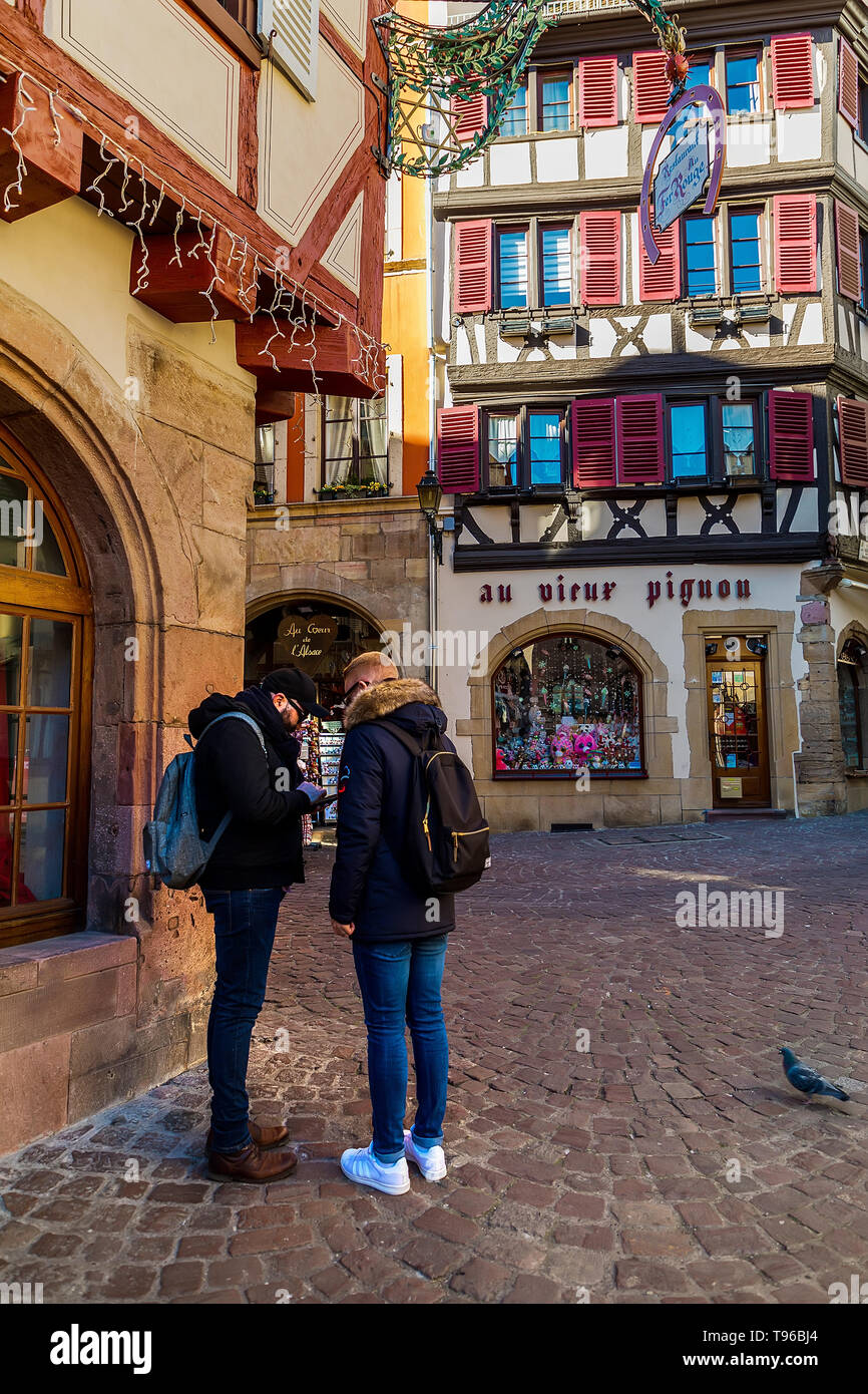 Colmar, Alsace, France, February 24, 2019.  Two man staing at cozy and beautiful streets of the French city on a sunny spring warm day - Stock Image