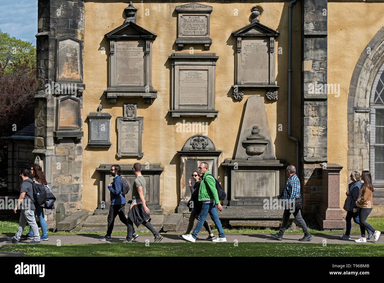 Trourists on a walking tour stroll by memorials on the wall of Greyfriars Kirk in Edinburgh, Scotland, UK. - Stock Image