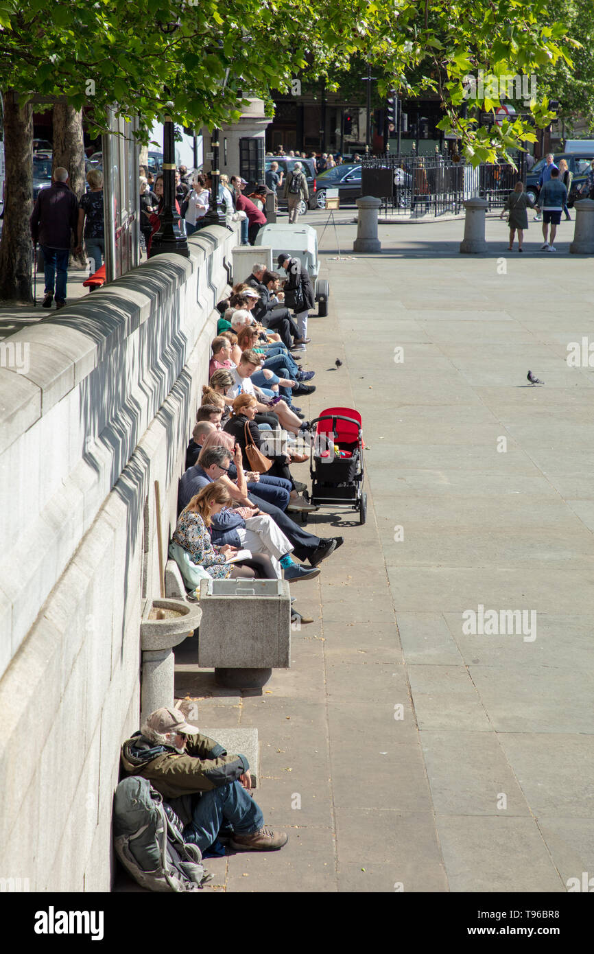Tourists and Londoners enjoying a day out and relax on Trafalgar Square, London, UK on a warm sunny afternoon in May. - Stock Image
