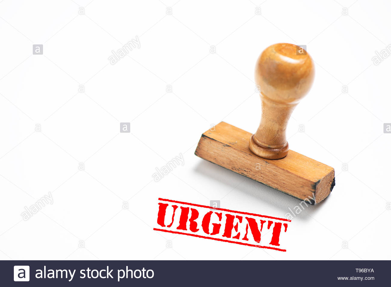 Rubber stamp with urgent sign on white background. Close up - Stock Image