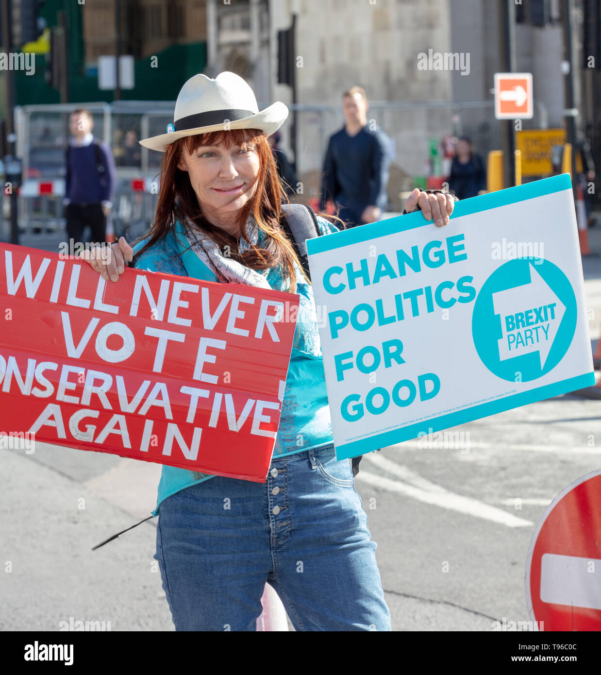 Female protester and member of the newly formed Brexit Party, demonstrates with two placards outside the House of Commons on Parliament Square, London Stock Photo