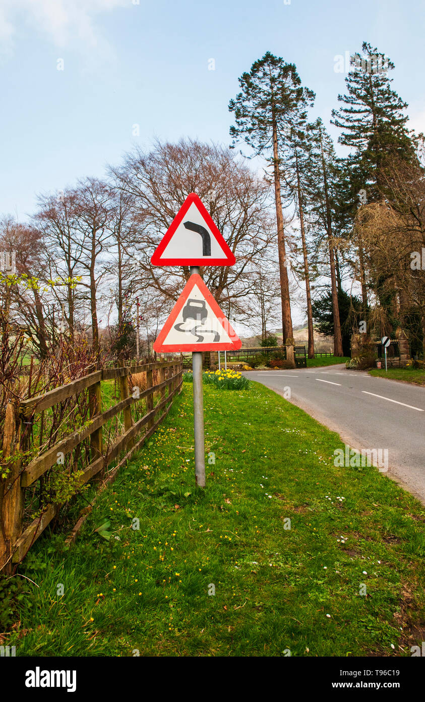 Traffic road warning signs Bend to left and Slippery road with National speed limit applies sign in distance - Stock Image