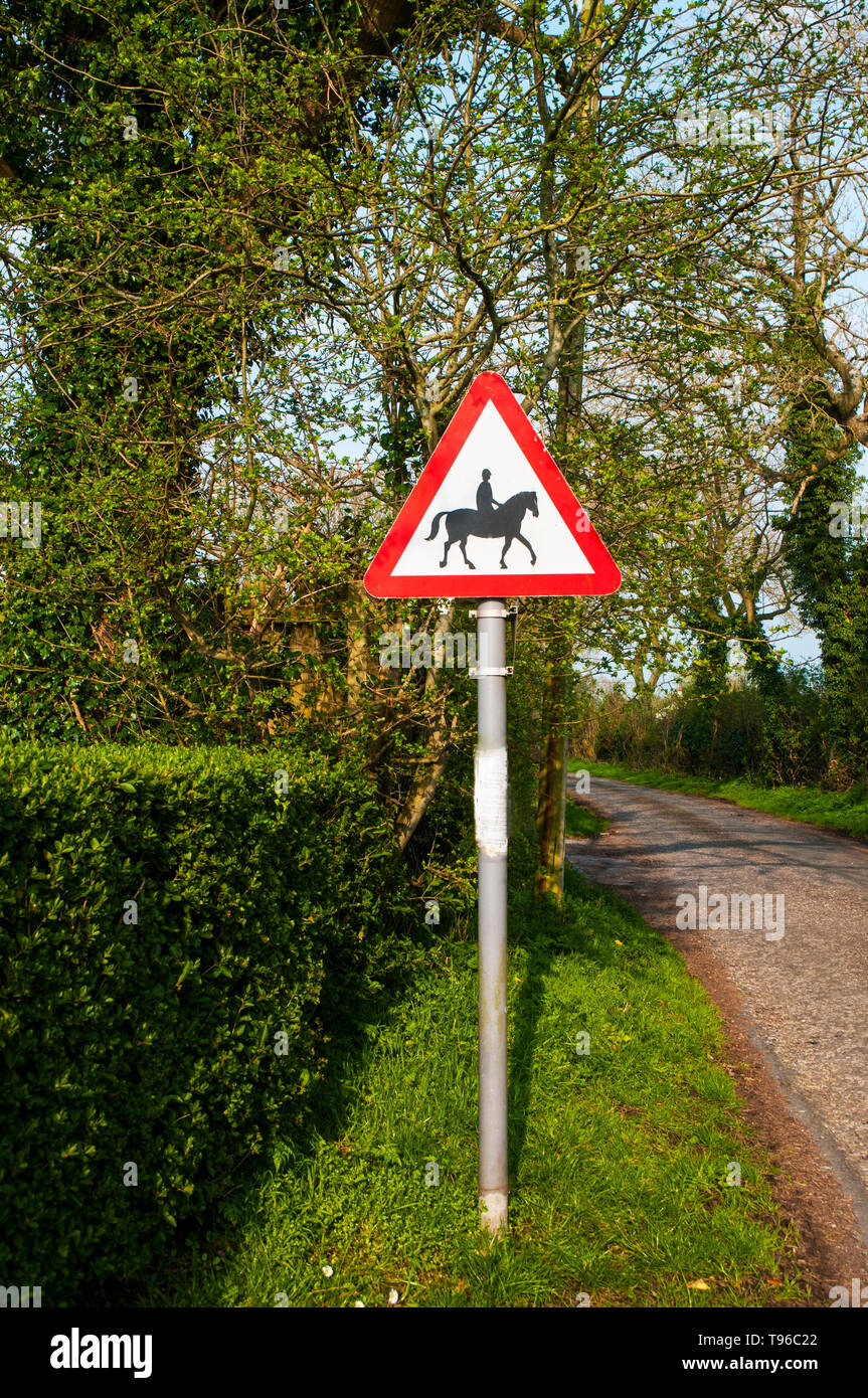 Road traffic warning sign to warn motorists to beware of horses and riders ahead around corner  Most likely to be seen in rural countryside - Stock Image