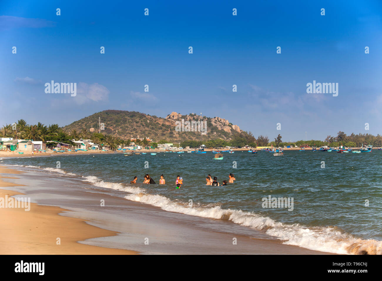 Locals people  swimming  in the sea, near Saigon Ninh Chu Resort on Phan Rang Beach,south china sea, Ninh Thuan, Vietnam - Stock Image
