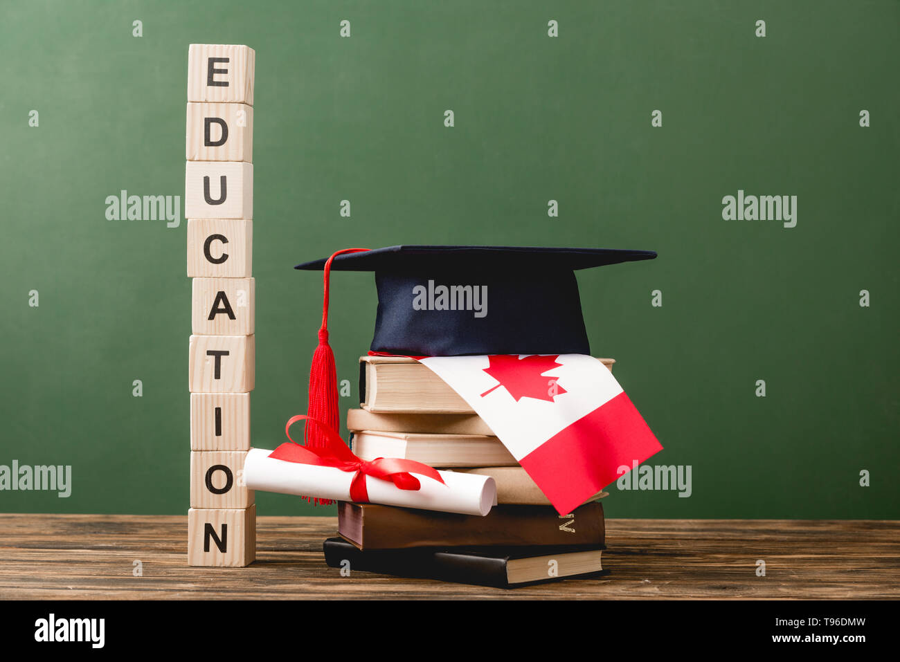 wooden blocks with letters, diploma, books, academic cap and canadian flag on wooden surface isolated on green - Stock Image