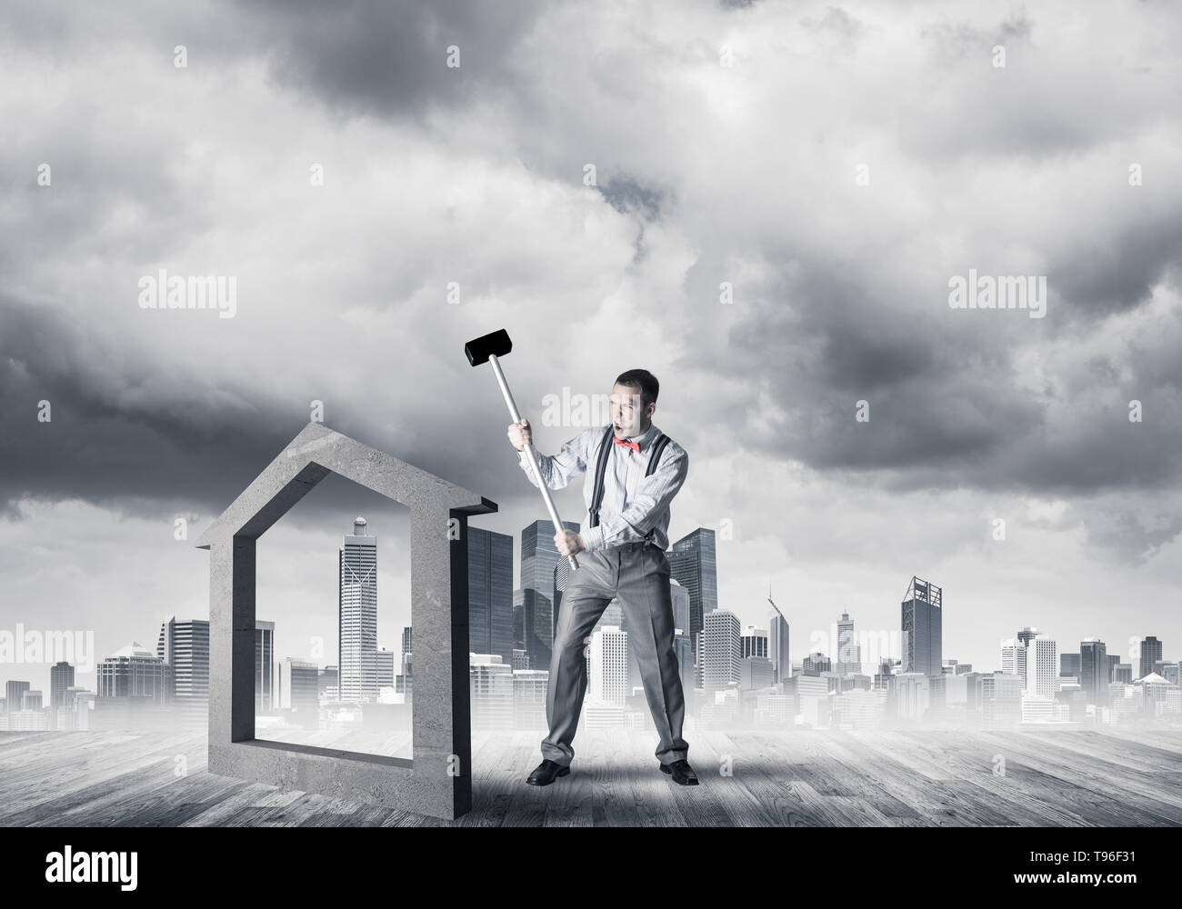Manager man crashing stone home as symbol for real estate insurance - Stock Image