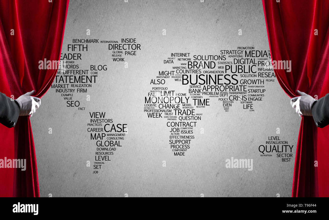World map behind drapery curtain and hand opening it - Stock Image