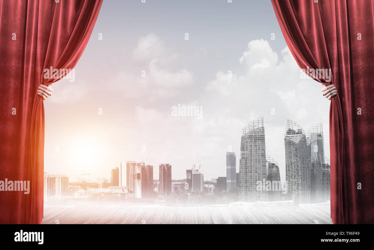 Business city in gray fog behind red curtain and hand holding it - Stock Image