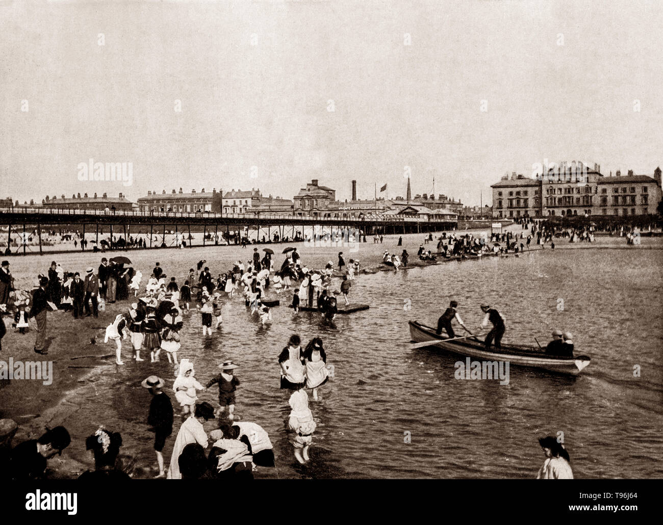 A late 19th Century view of  holiday makers in Southport, a Lancashire seaside town lying on the Irish Sea coast and is fringed to the north by the Ribble estuary.  At the turn of the 19th century, the area became popular with tourists, a rapid growth that largely coincided with the Industrial Revolution and the Victorian era. Town attractions include Southport Pier, one of the earliest pier structures to be erected using iron, with its Southport Pier Tramway, the second longest seaside pleasure pier in the British Isles - Stock Image