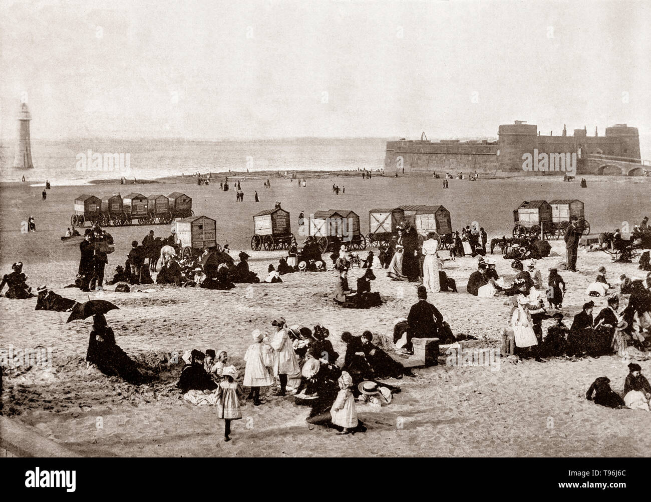 A late 19th Century view of  holiday makers beside bathing machines at New Brighton. A seaside resort on the Wirral peninsula in Merseyside, England, it has sandy beaches lining the Irish Sea on which stands Perch Rock battery completed in 1829. During the latter half of the 19th century, New Brighton developed as a very popular seaside resort serving Liverpool and the Lancashire industrial towns, and many of the large houses were converted to inexpensive hotels. - Stock Image
