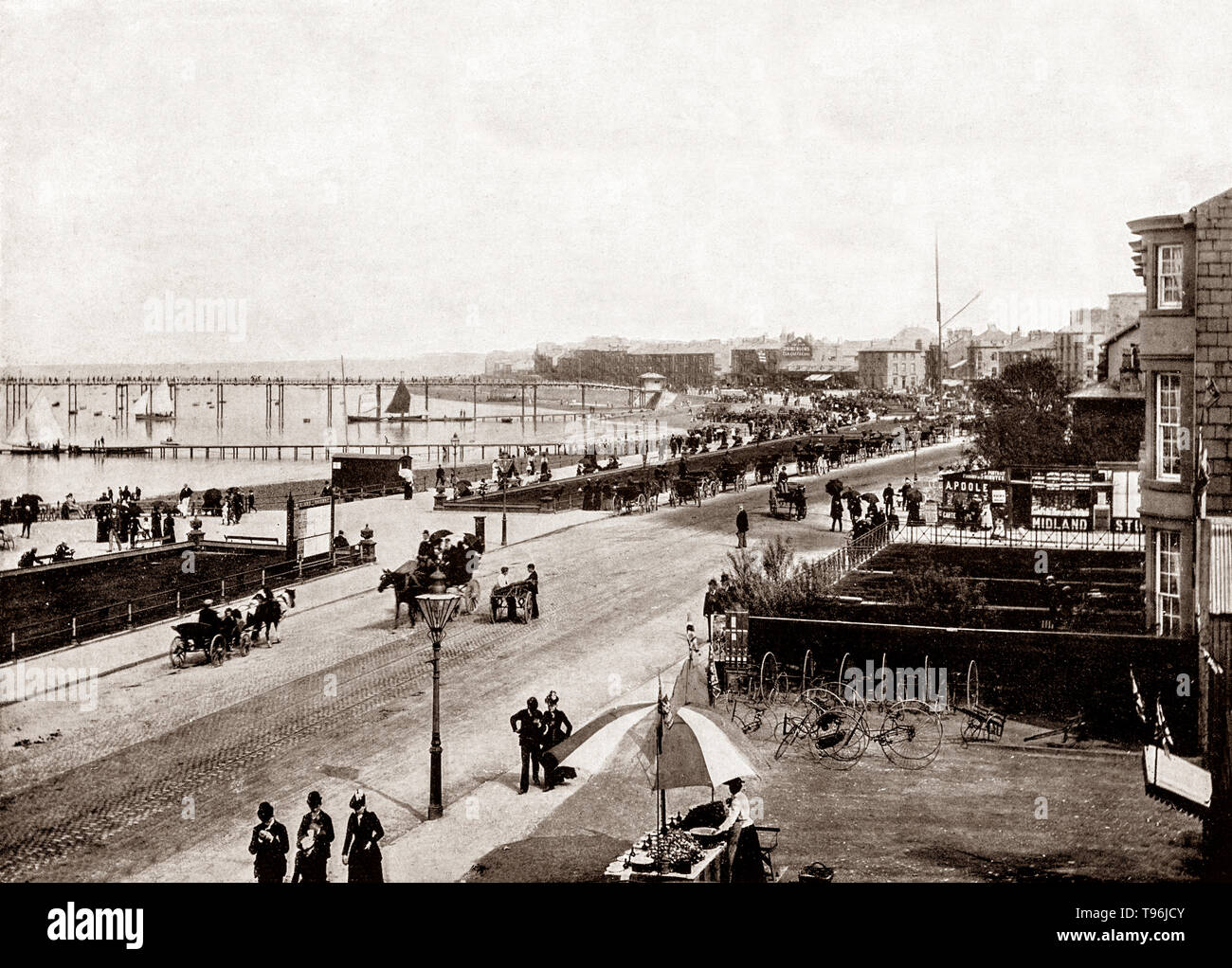 A late 19th Century view of  the beach at Morecambe, a coastal town on Morecambe Bay in Lancashire, England. While the resort of Blackpool attracted holiday-makers predominantly from the Lancashire mill towns, Morecambe had more visitors from Yorkshire (due to its railway connection) and Scotland. Mill workers from Bradford and further afield in West Yorkshire would holiday at Morecambe, with some retiring there. - Stock Image