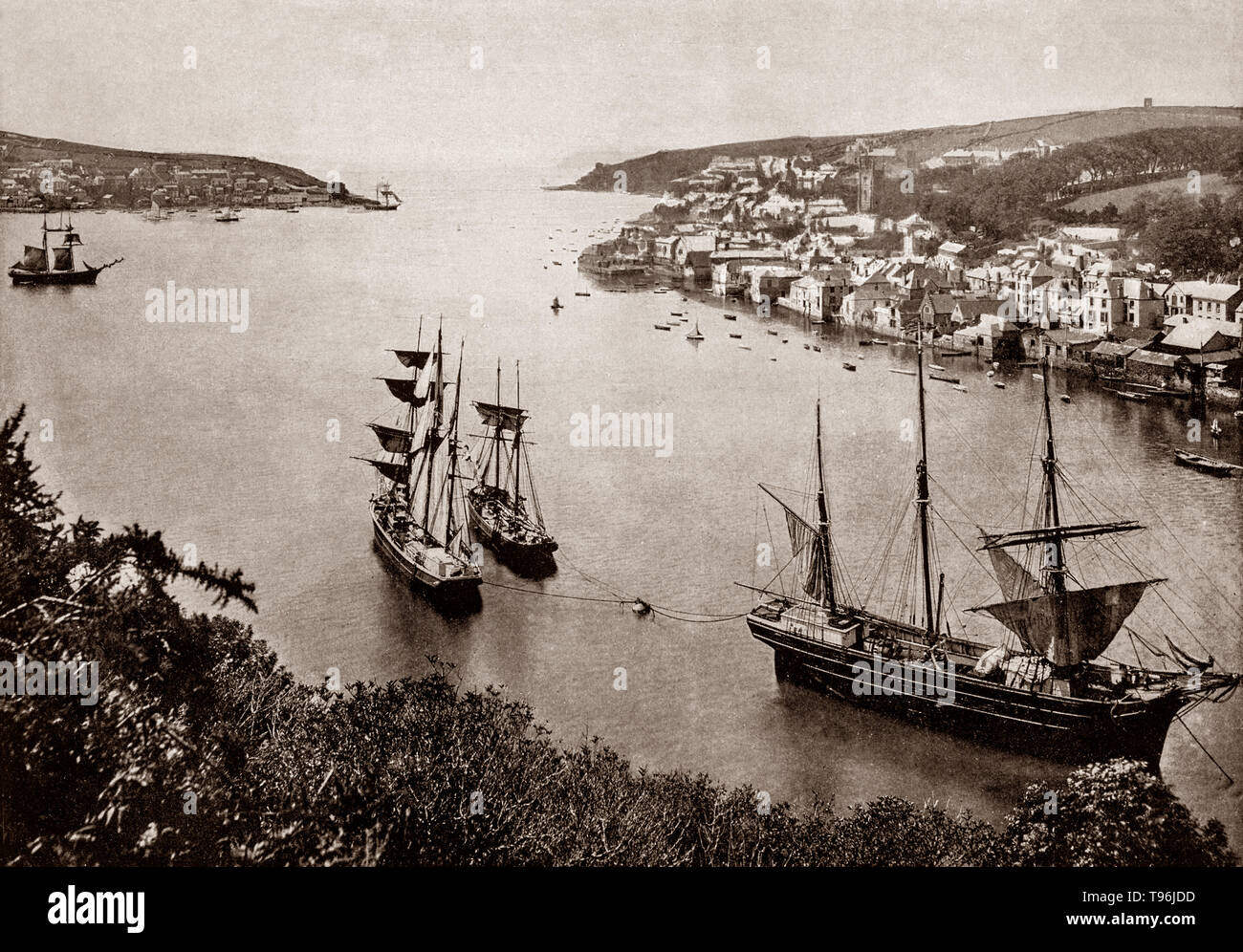 A late 19th Century view of  shipping in the harbour at Fowey, a small town and cargo port at the mouth of the River Fowey in south Cornwall, England. The estuary of the River Fowey forms a natural harbour which enabled the town to become an important trading centre. Privateers also made use of the sheltered harbourage. The Lostwithiel and Fowey Railway brought China clay here for export. - Stock Image