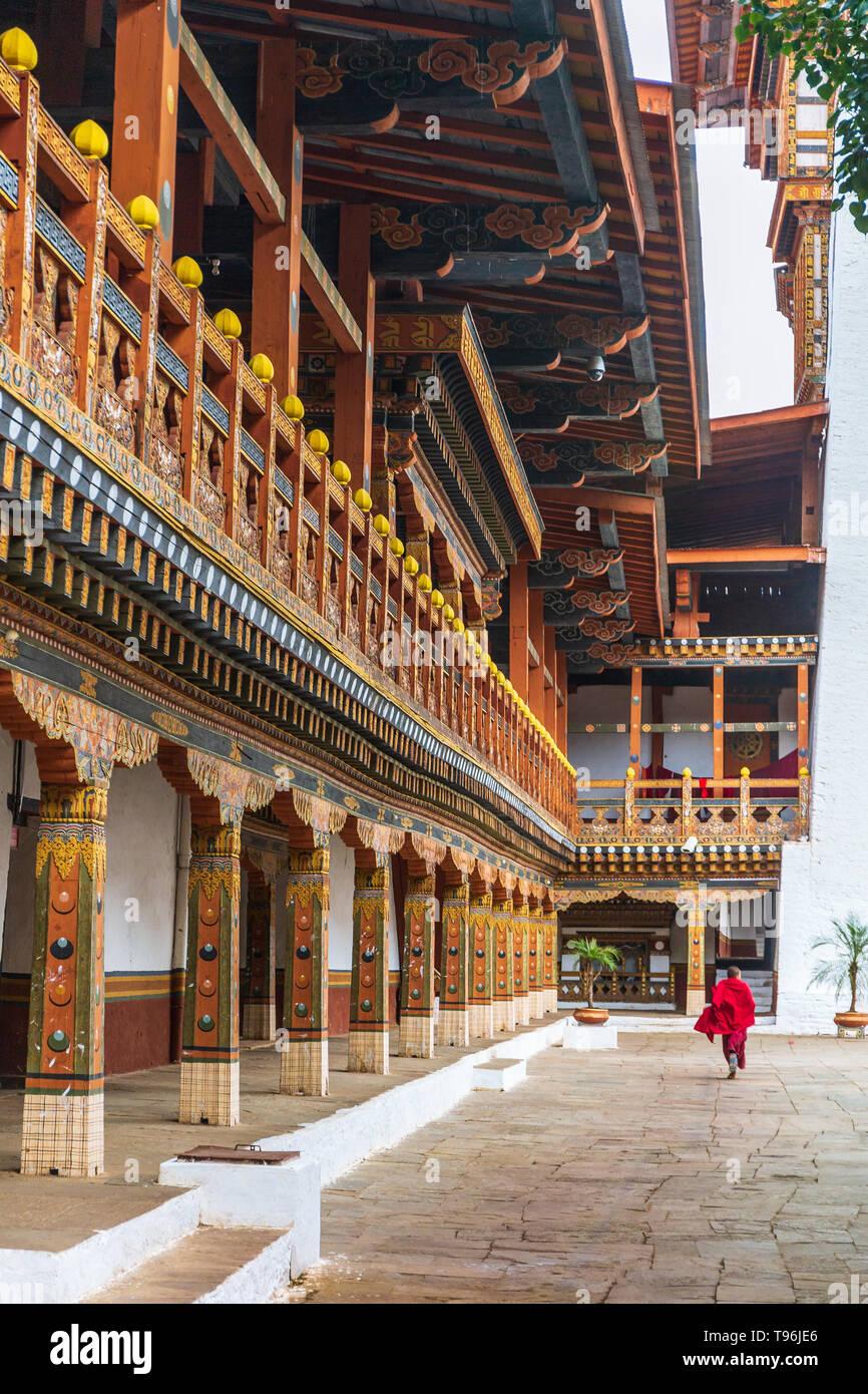 Buddhist monk running through the courtyard of the monastery and fortress Punakha Dzong, Bhutan - Stock Image