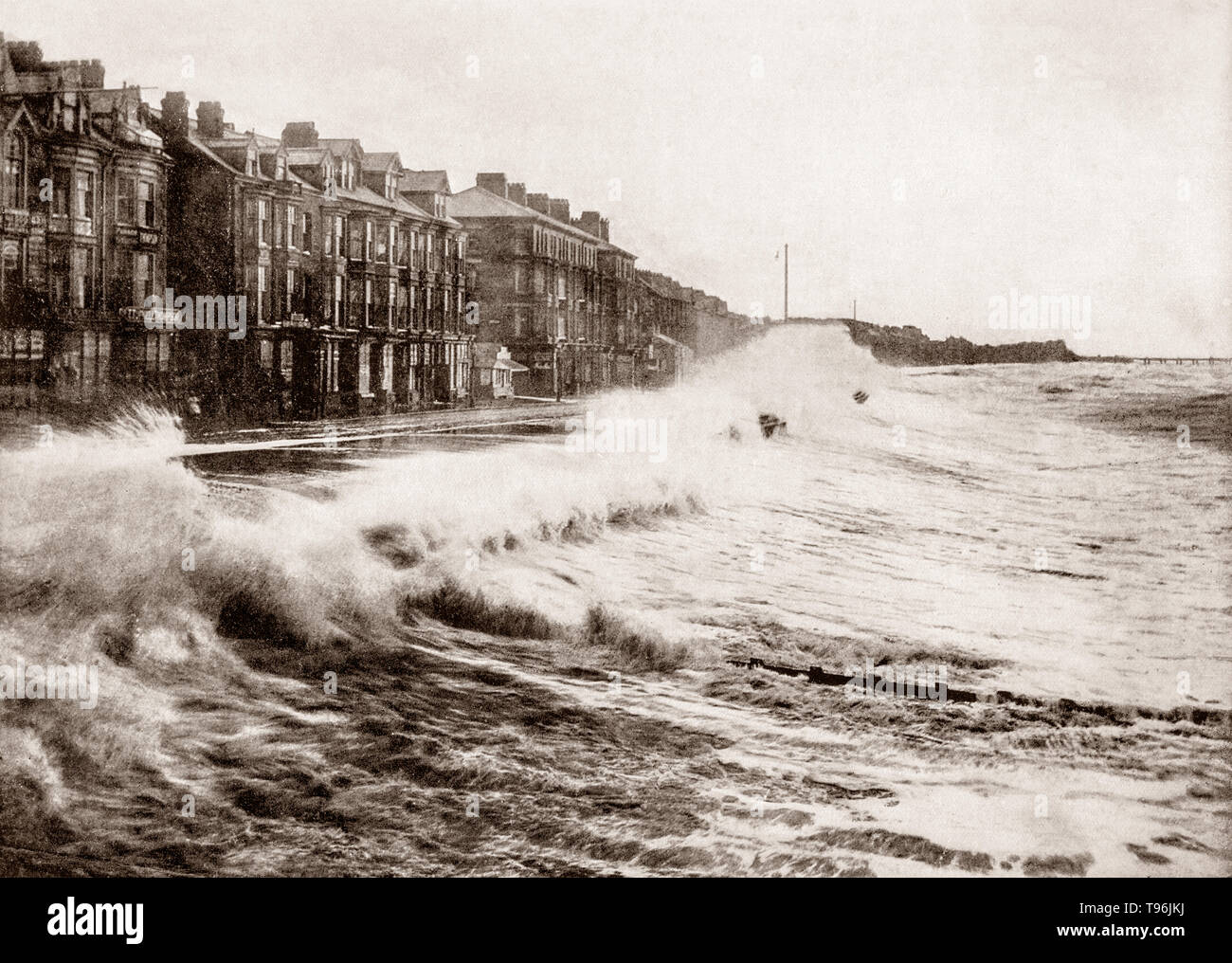 A late 19th Century view of  stormy seas battering the seafront in Blackpool, a seaside resort on the Lancashire Irish Sea coast, between the Ribble and Wyre estuaries, in North West England.  It became fashionable in the middle of the 18th century due to the practice of sea bathing to cure diseases, with the completion of a branch railway line to Blackpool. Tourist growth was intensified by the practice among the Lancashire cotton mill owners of closing the factories for a week every year to service and repair machinery. - Stock Image