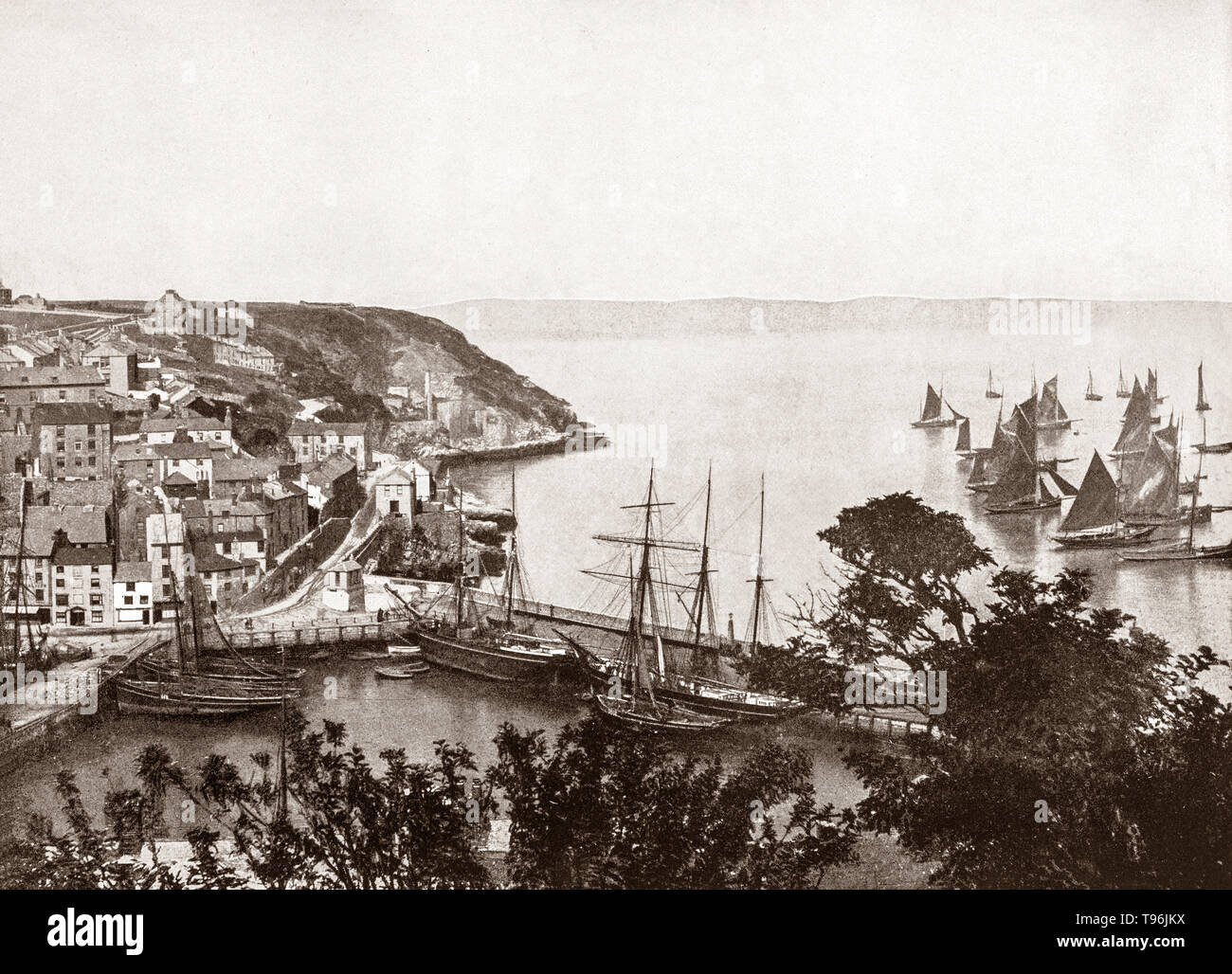 A late 19th Century view of shipping in the harbour in Brixham, a small fishing town in the district of Torbay in the county of Devon, in the south-west of England.  For many years Brixham was the largest fishing port in the south west of England and its boats helped to establish the fishing industries of Hull, Grimsby and Lowestoft. Some of the 300  individually owned trawling vessels from Brixham can be seen heading out to sea. - Stock Image