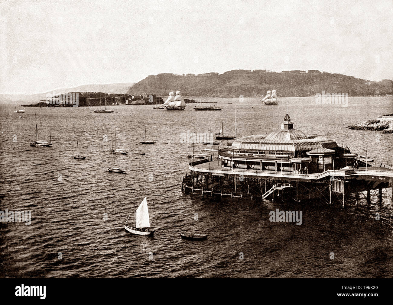 A late 19th Century view of yachts and sailing beyond the promenade pier, opened in 1884, in Plymouth, a port city situated on the south coast of Devon, England.  Enclosing the city are the mouths of the river Plym and river Tamar, which are naturally incorporated into Plymouth Sound to form a boundary with Cornwall. - Stock Image