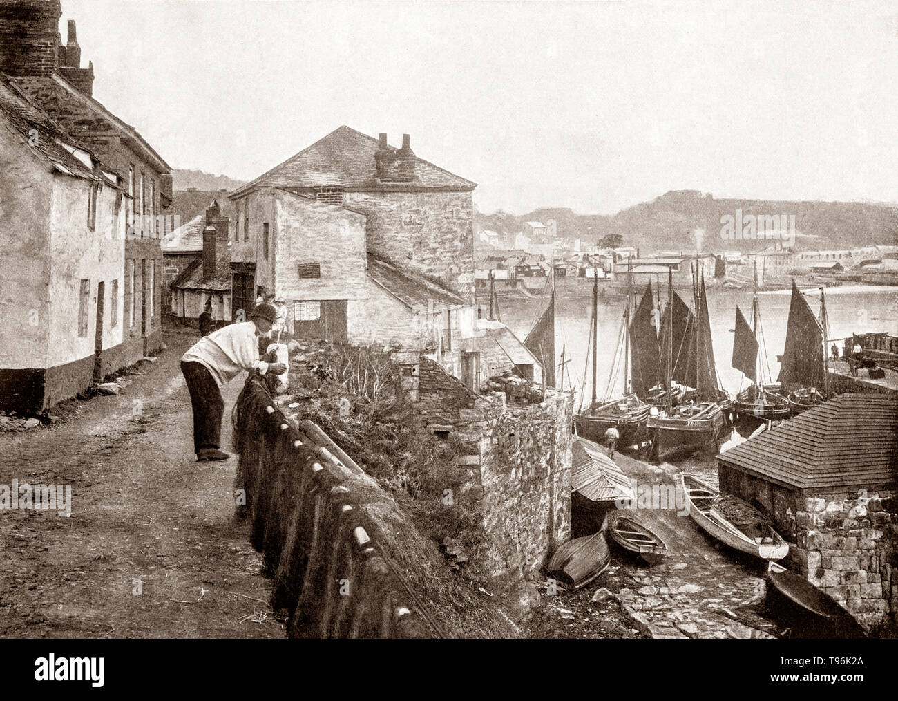 A late 19th Century view of Newlyn, a seaside town and fishing port in south-west Cornwall, England. It lies on the shore of Mount's Bay and forms a small conurbation with the neighbouring town of Penzance. The principal industry was fishing, some of which can be seen in the the harbour. - Stock Image
