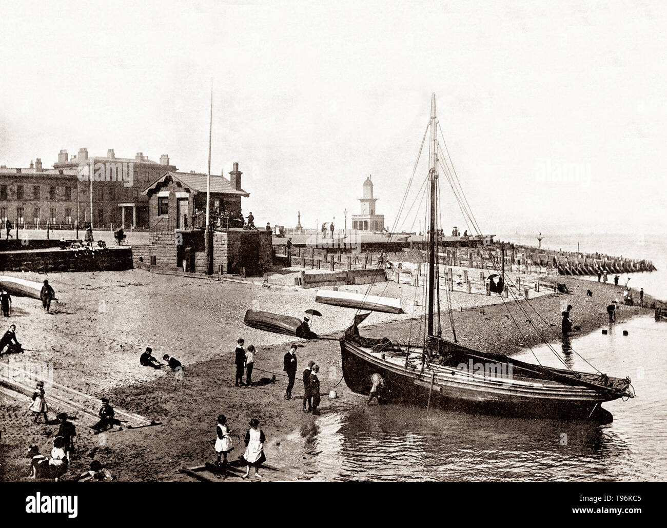 A late 19th Century view of  a sailing boat, drawn up on the beach at Fleetwood, a coastal town in Lancashire, England, at the northwest corner of the Fylde. The town expanded greatly with the growth of the fishing industry, and passenger ferries to the Isle of Man, to become a deep-sea fishing port. - Stock Image