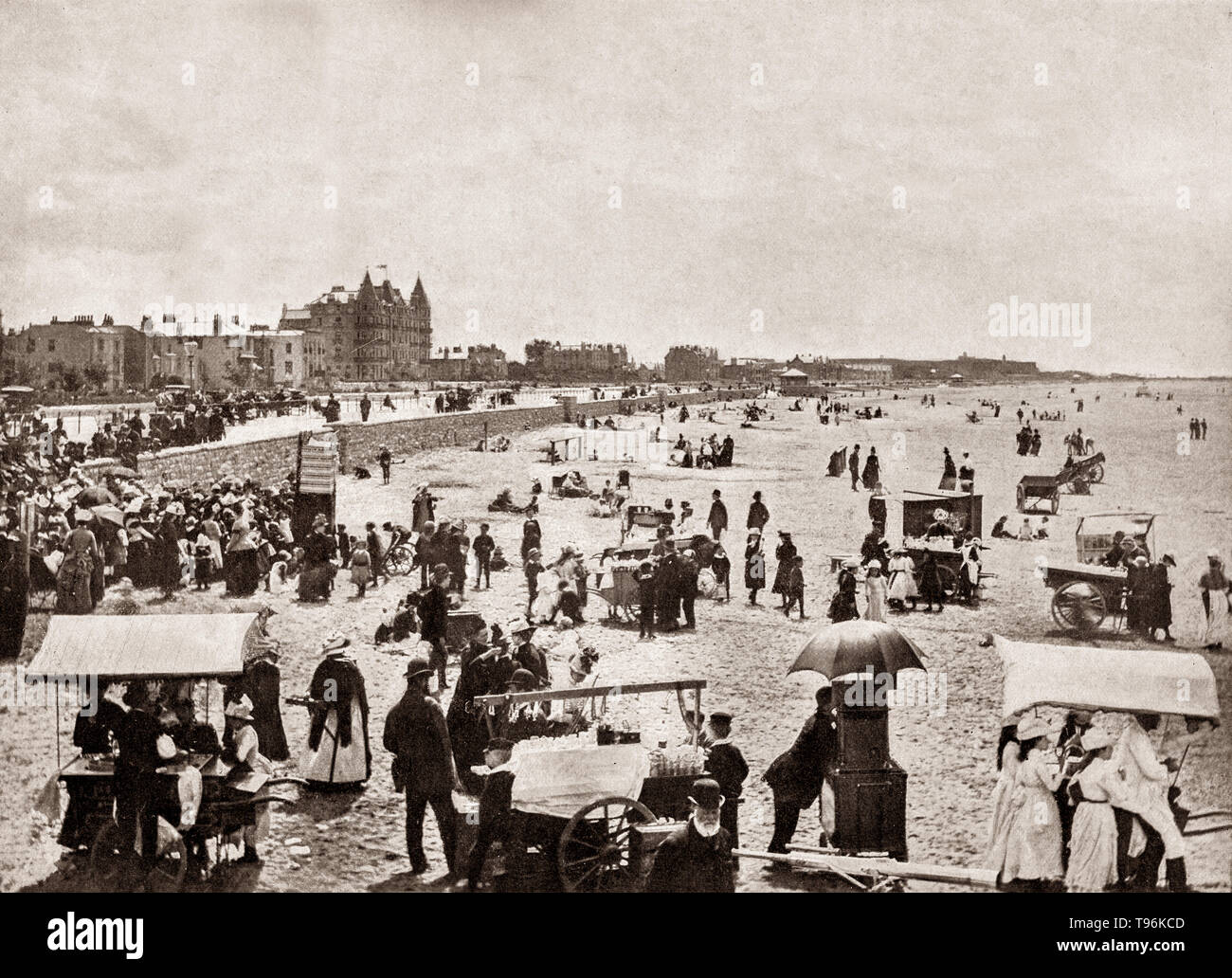 A late 19th Century view of a crowded beach at Weston-Super-Mare, aka Weston, a seaside town on the Bristol Channel in North Somerset, England. Early in the 19th century, Weston was a small village of about 30 houses, located behind a line of sand dunes fronting the sea, and grew with the Victorian era boom in seaside holidays.  Mining families came across the Bristol Channel from South Wales by paddle steamer to enjoy its beach,  amusement arcades, tea rooms, amusement rides and a photographic studio. - Stock Image