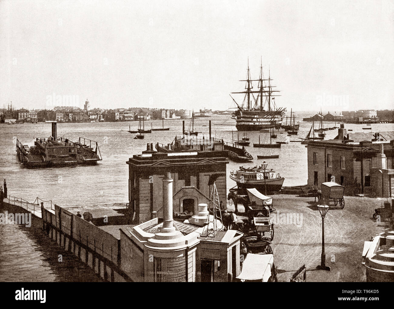 A late 19th Century view of an early small car ferry dwarfed by Admiral Nelson's flagship 'Victory' floating in the vast harbour in Portsmouth. a port city in Hampshire, England. During the 19th century,  the world's first mass production line was set up in Portsmouth Dockyard's Block Mills, making it the most industrialised site in the world and birthplace of the Industrial Revolution. Portsmouth was also the most heavily fortified town in the world, and was considered 'the world's greatest naval port' at the height of the British Empire throughout Pax Britannica. - Stock Image