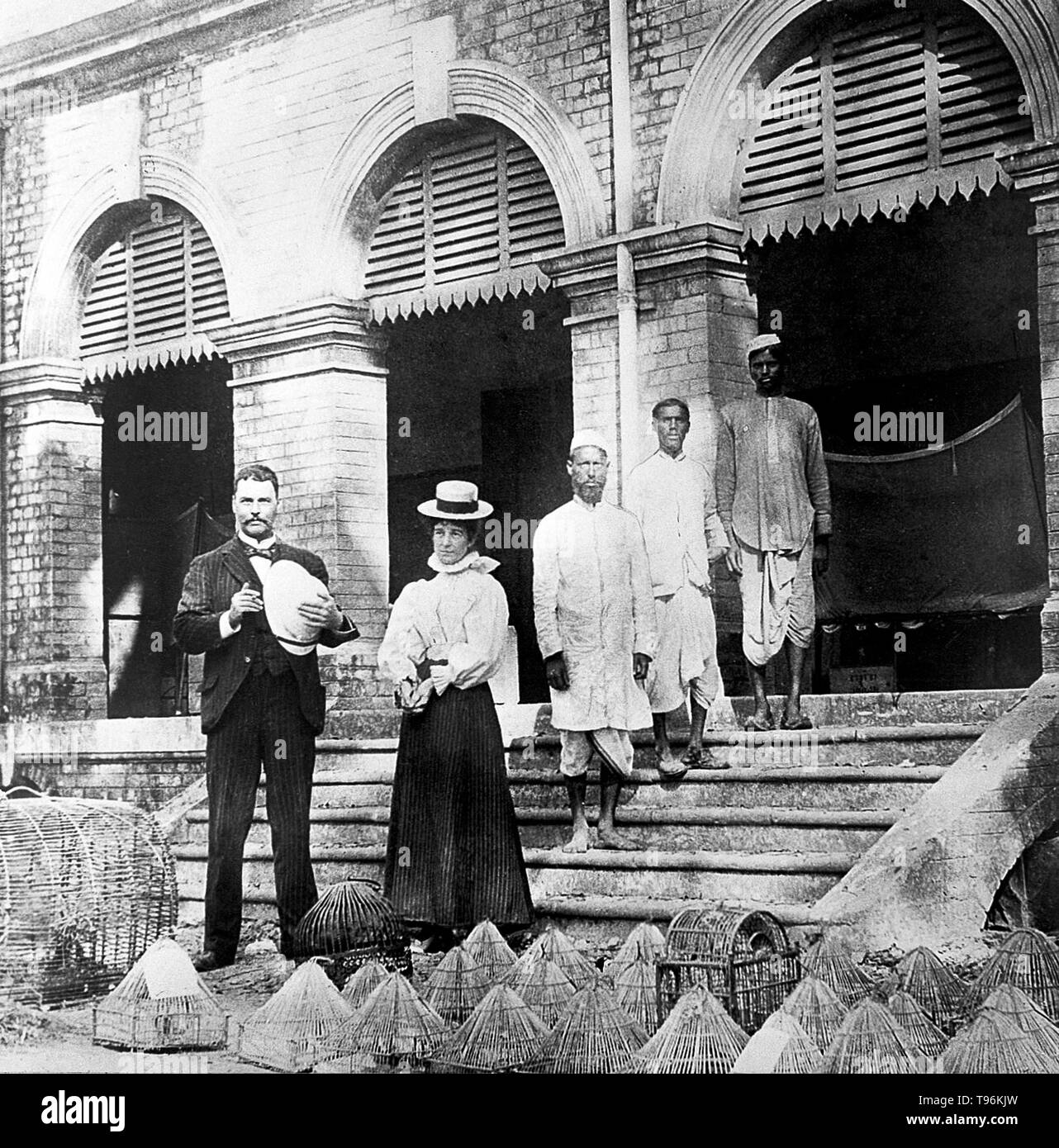Ross on the steps of laboratory in Calcutta, 1898. With Mrs Ross, Mahomed Bux and laboratory assistants in the foreground, cages for malarial birds. Sir Ronald Ross (May 13, 1857 - September, 16 1932) was a British doctor and polymath. He was born in India where his grandfather contracted malaria and he vowed at an early age to find a cure. At the age of eight, he was sent to England for his education. He began to study medicine in 1875, passed his final examination in 1880 and joined the Indian Medical Service in 1881. He began his research into malaria in 1892. In 1897 his discovery of the m - Stock Image