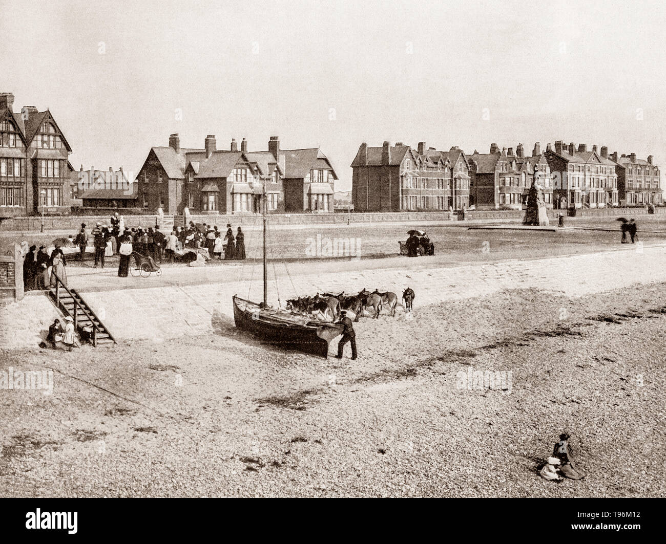 A late 19th Century view of a small sailing boat, donkeys and toursts on the beach at Lytham St Annes aka St Annes-On-Sea, a seaside resort on the Fylde coast of Lancashire, England, south of Blackpool on the Ribble Estuary.  On 14 October 1874 the St Anne's-on-the-Sea Land and Building Company Ltd was registered, mainly at the instigation of Elijah Hargreaves, a wealthy Lancashire mill owner from Rawtenstall to develop the area as a resort for people from Lytham and Southport. - Stock Image