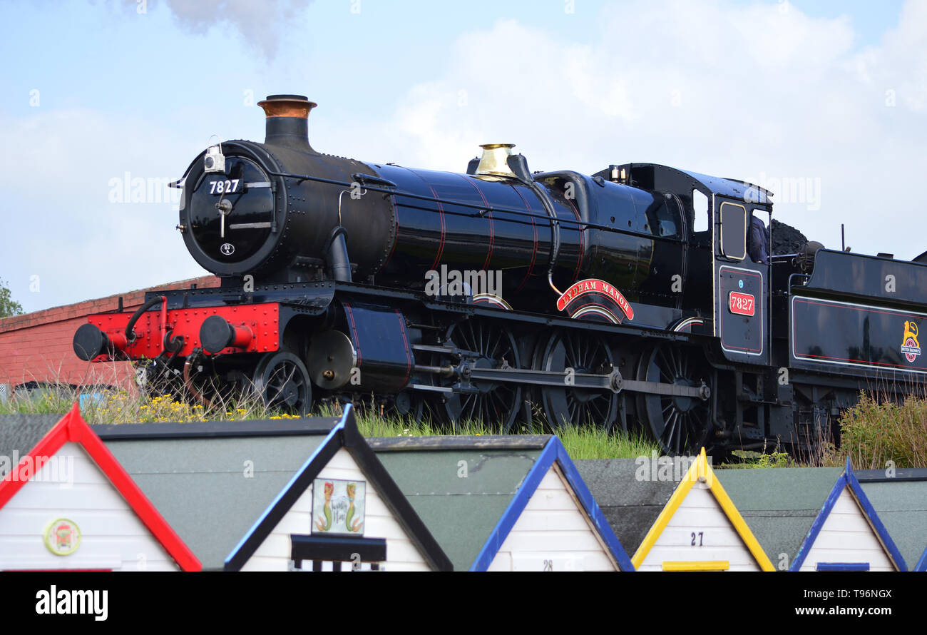 Lydham Manor Steam Engine 7827 above beach huts, Goodrington Sands, Torbay, Devon, England - Stock Image