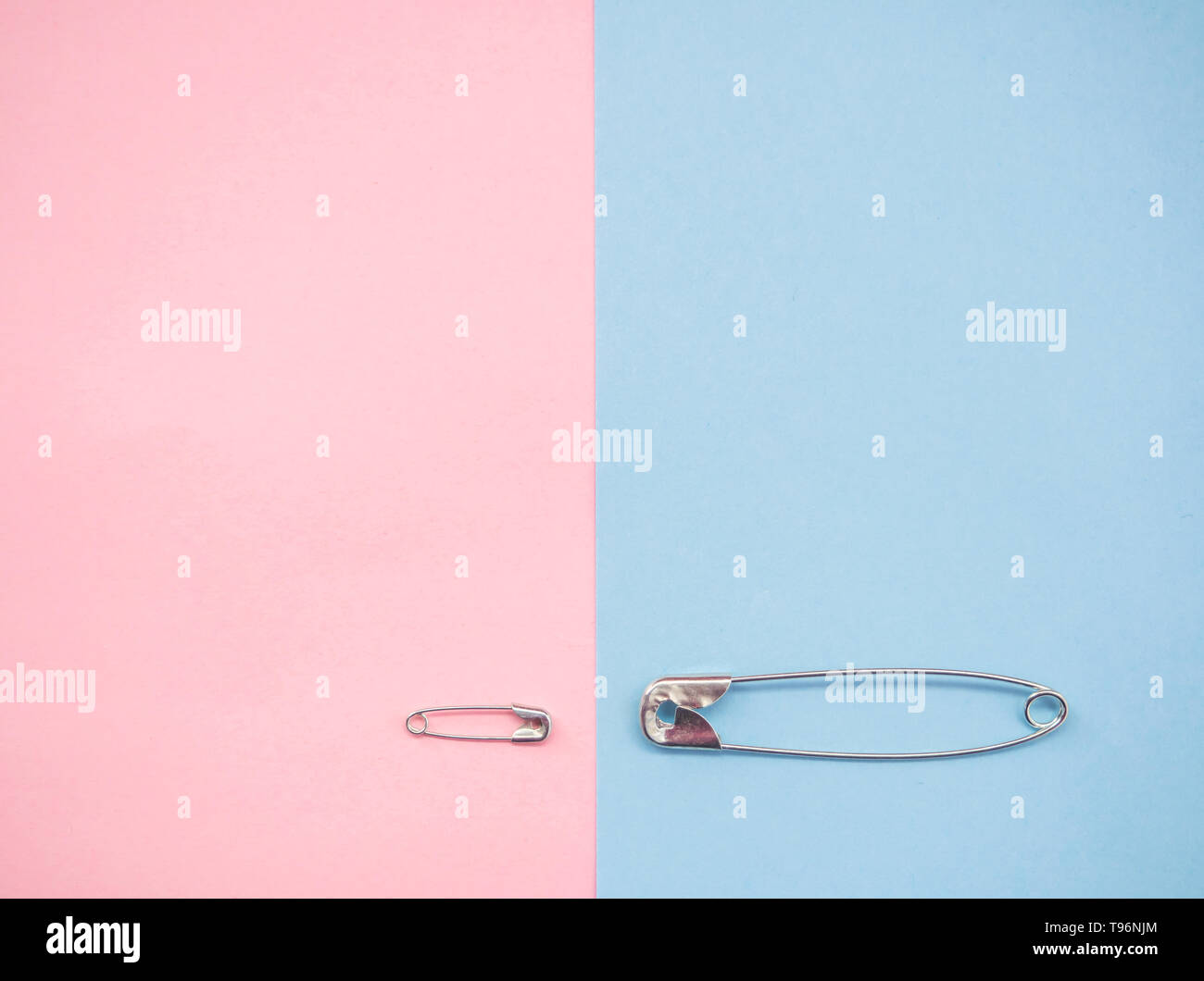 Two safety pins representing a man and a woman. Concept of machismo and feminism - Stock Image