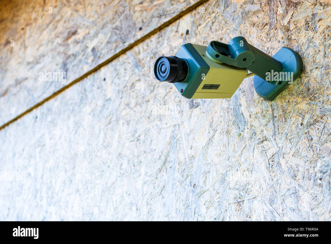 Fake security camera placed on a wooden OSB (oriented strand board) in sub-urban neighborhood. Concept for private home, security, with space for text - Stock Image